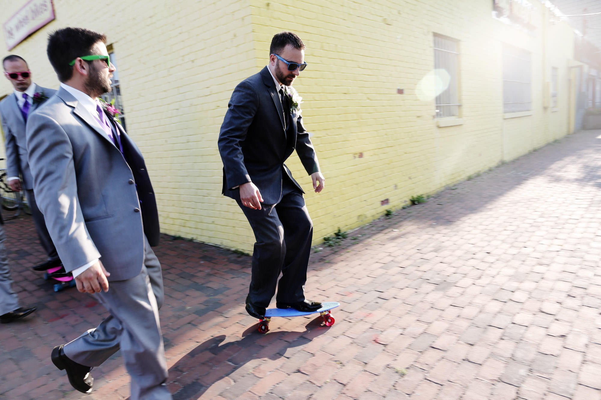The groom rides his skateboard through Alexandria before his Topedo Factory wedding.