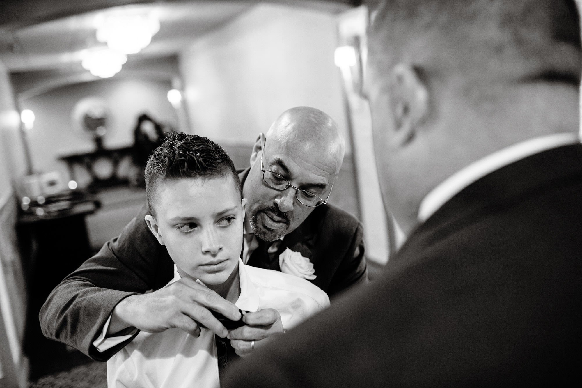 The father of the bride helps a young man put on his tie.