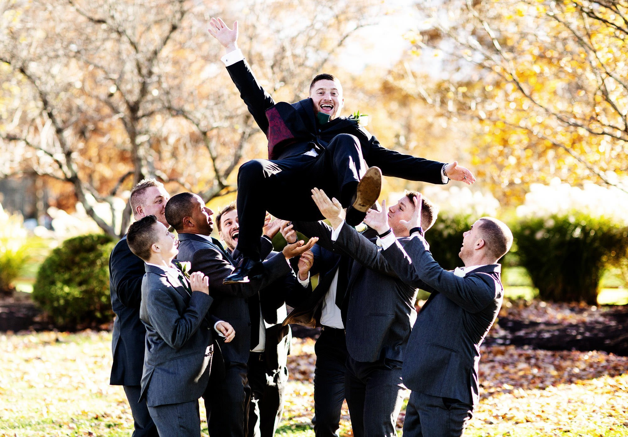 The groomsmen toss the groom in the air during his Villa at Ridder Country Club Wedding.