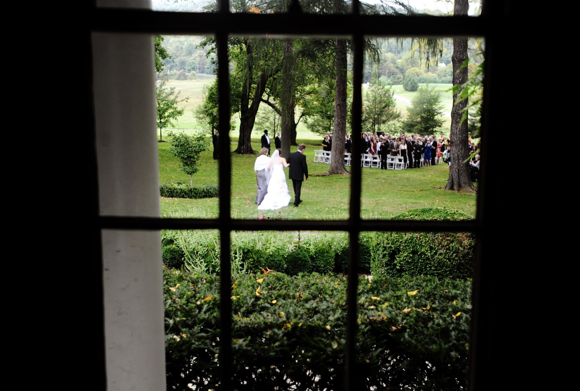 The bride is escorted by her parents to the ceremony space during her Whitehall Estate wedding.