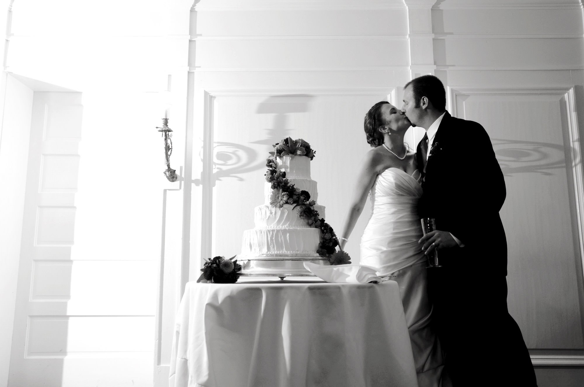 The bride and groom kiss before cutting their wedding cake at Whitehall Estate in Bluemont, VA.