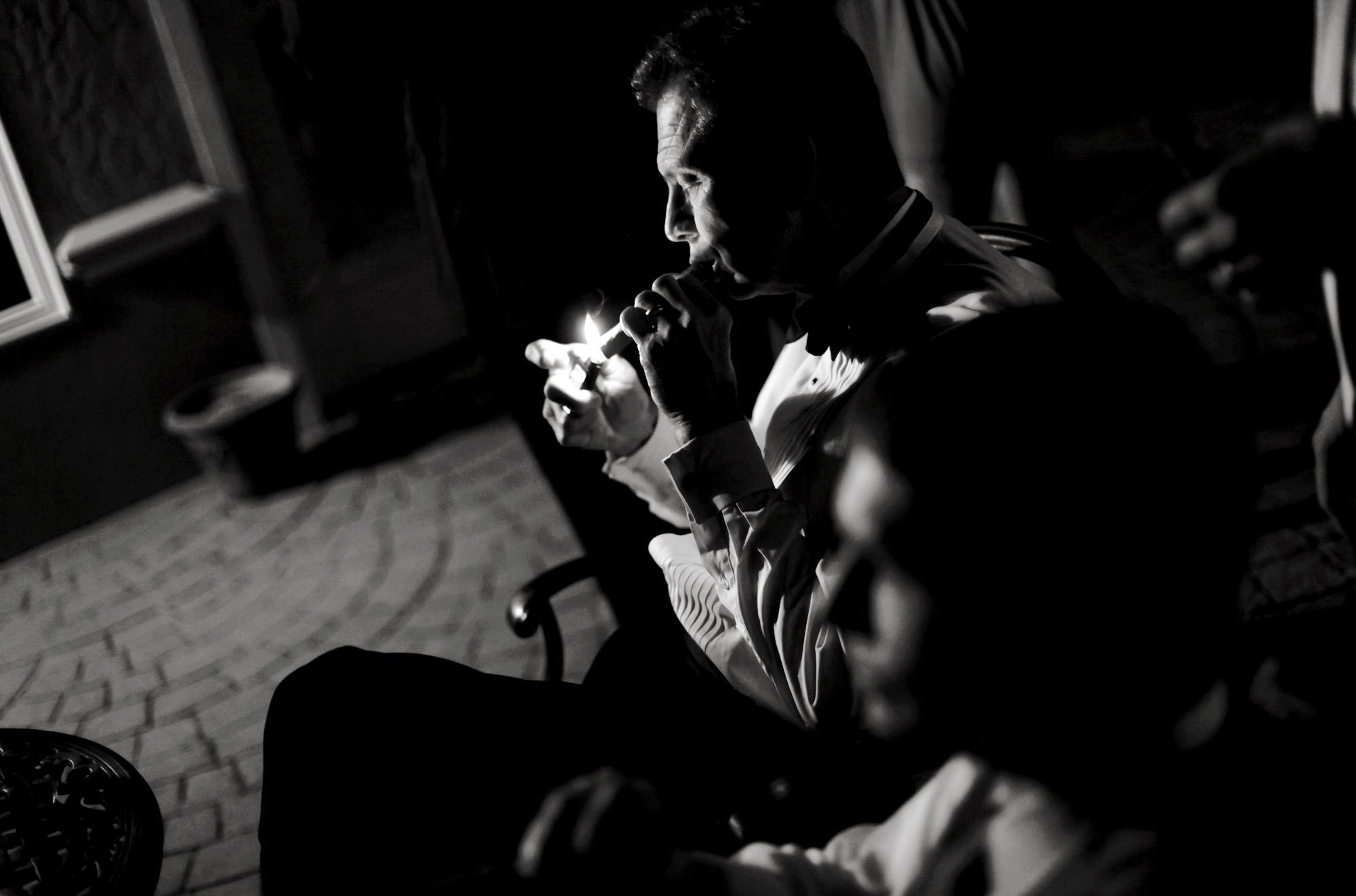 The father of the bride smokes a cigar during the wedding reception at Whitehall Estate in Bluemont, VA.