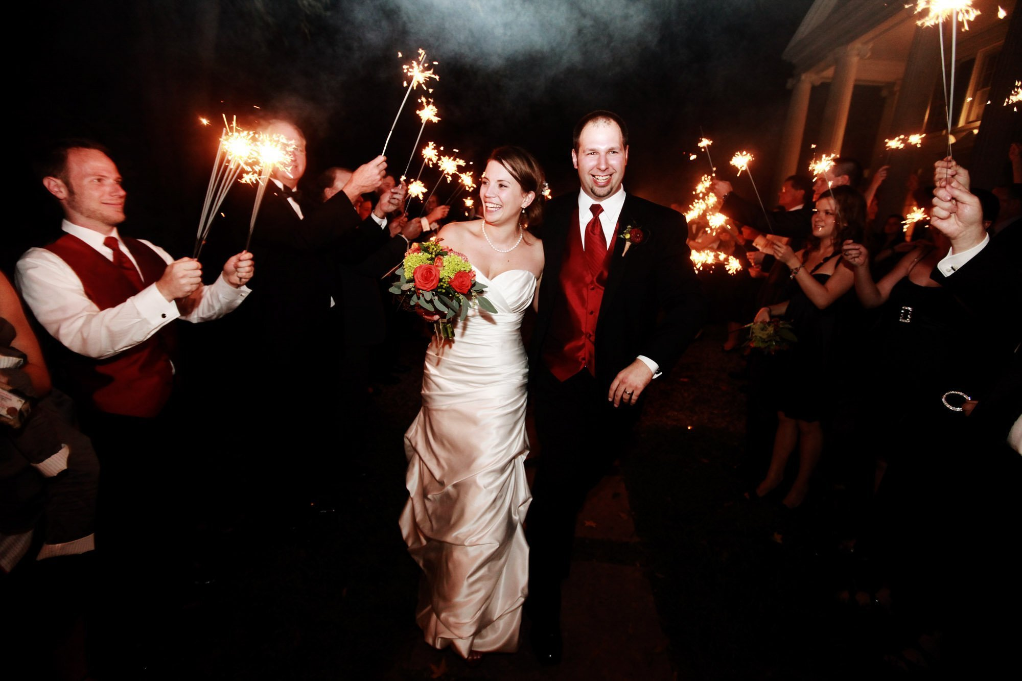The bride and groom walk through their sparkler sendoff following their Whitehall Estate wedding.