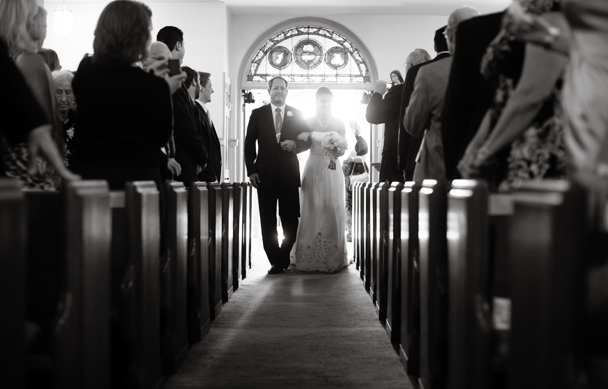The bride walks down the aisle during her wedding ceremony at St. Mary's Catholic Church in Rockville, MD.