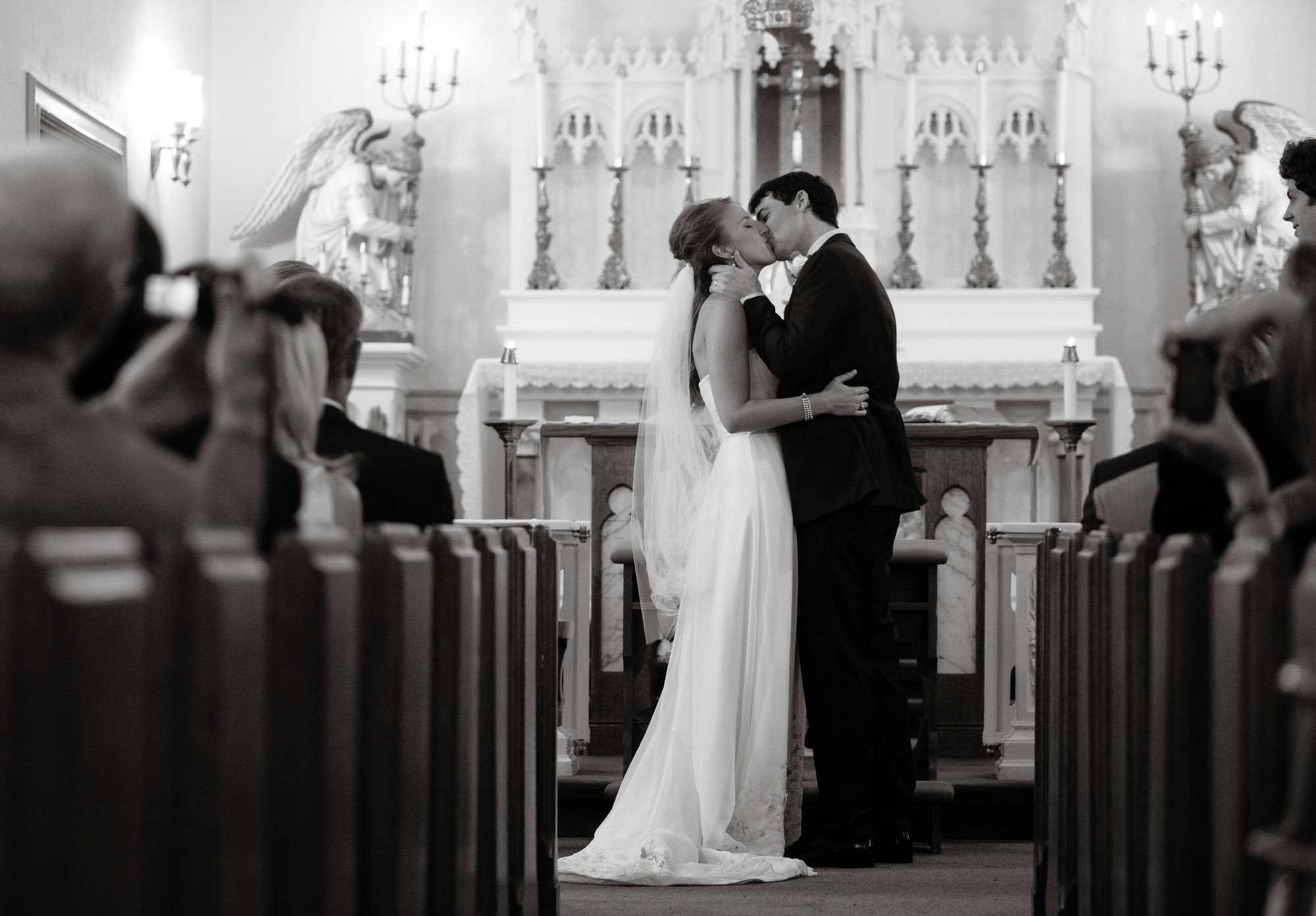 The bride and groom share their first kiss at St. Mary's Catholic Church in Rockville, MD.