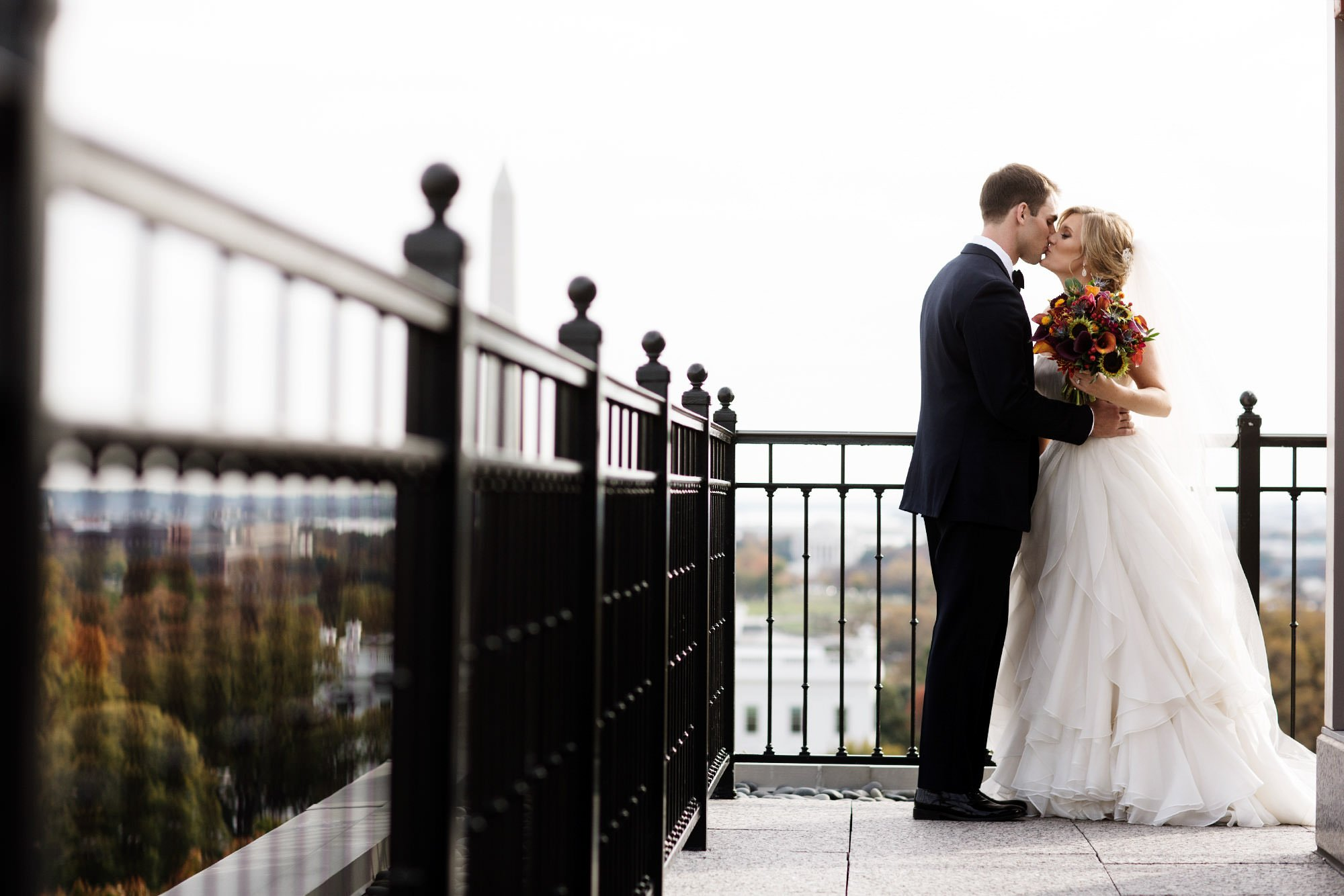 The bride and groom kiss on the patio of the Hay Adams Hotel in Washington, DC before their wedding ceremony.
