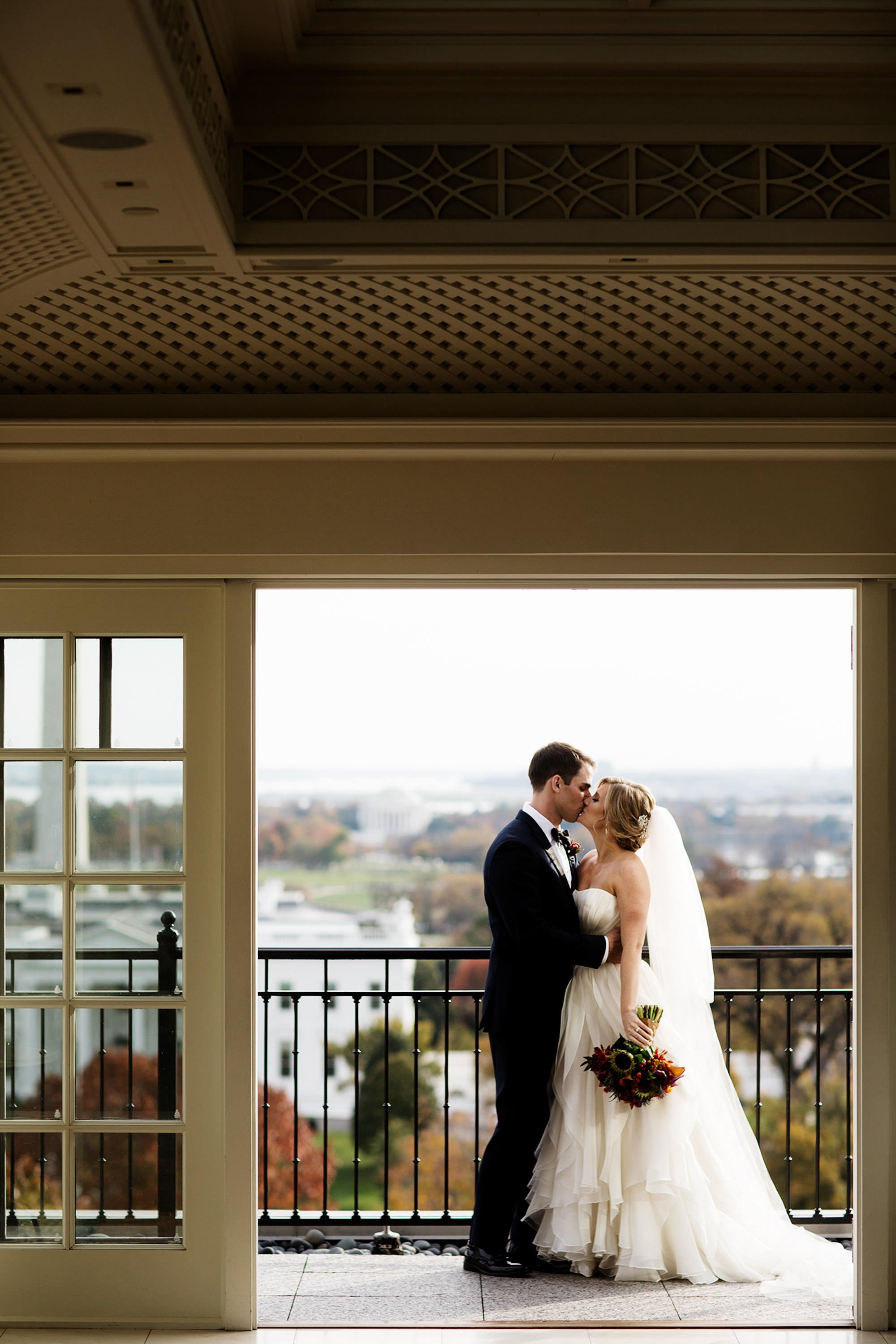 The bride and groom kiss on the patio of the Hay Adams hotel in Washington, DC before the wedding ceremony.