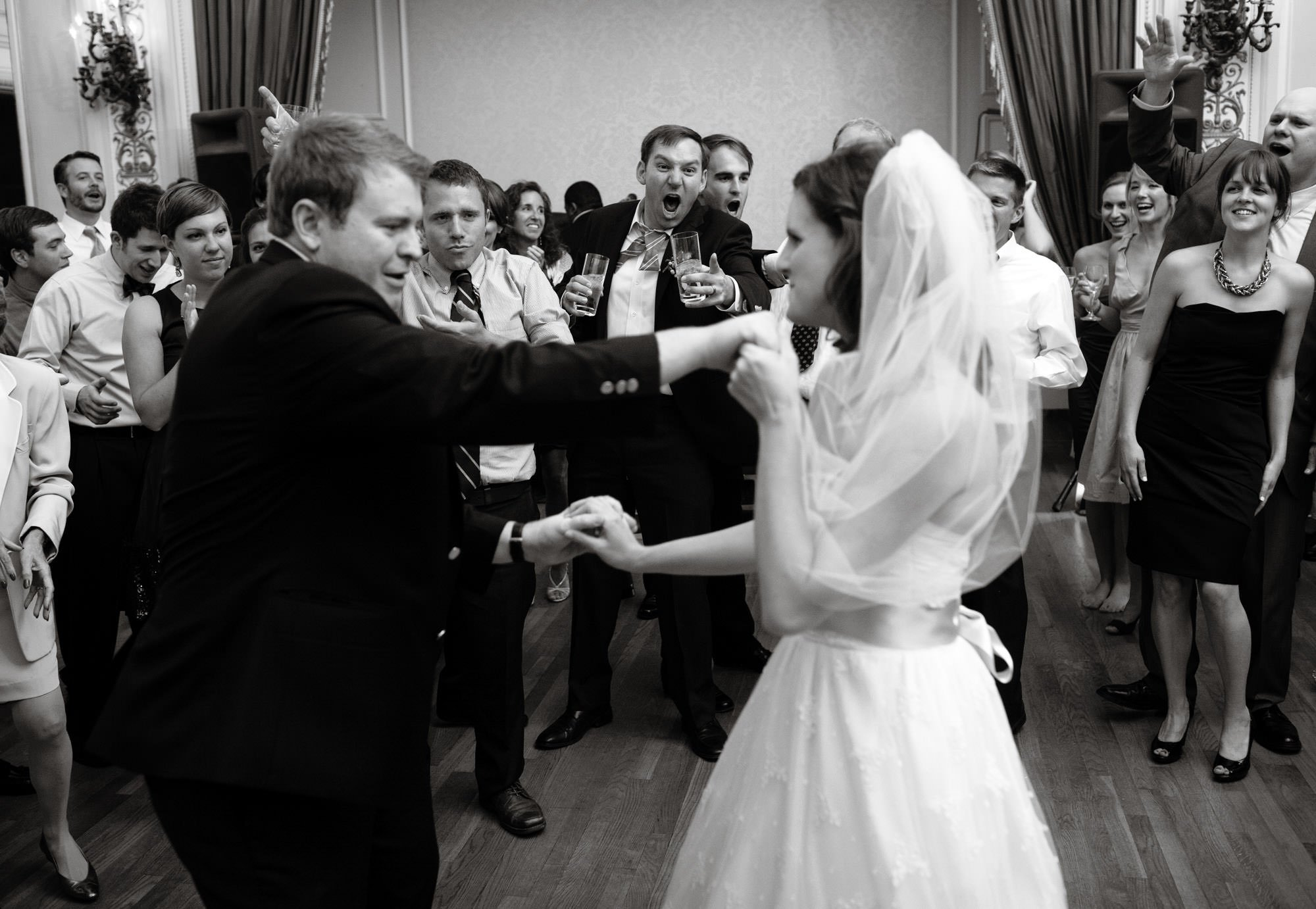 Guests cheer on the bride and groom during their first dance at their Sulgrave Club wedding reception.