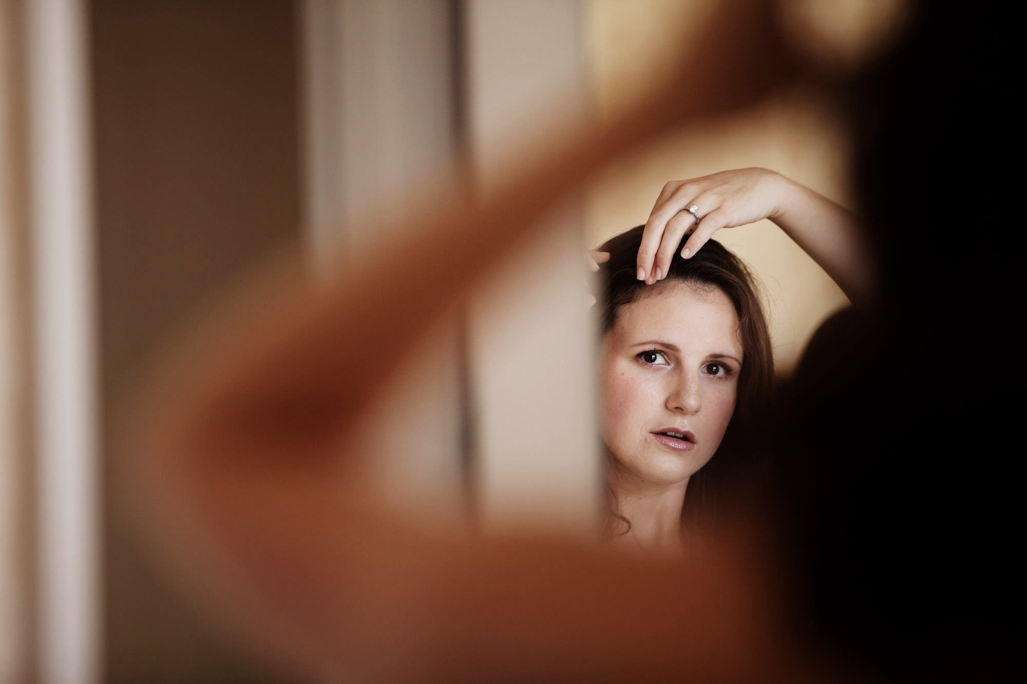 The bride looks at herself in the mirror before the Washington National Cathedral wedding ceremony.