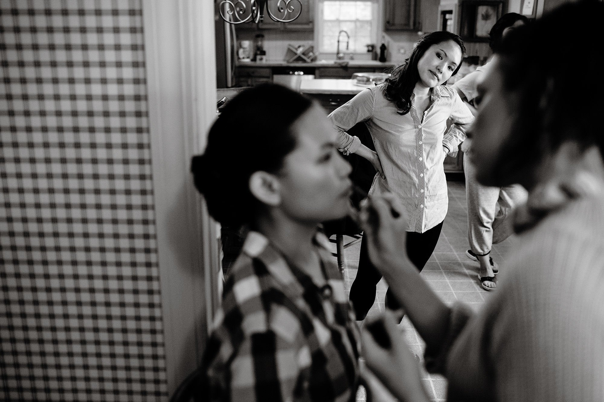 A bridesmaid watches as makeup is applied.