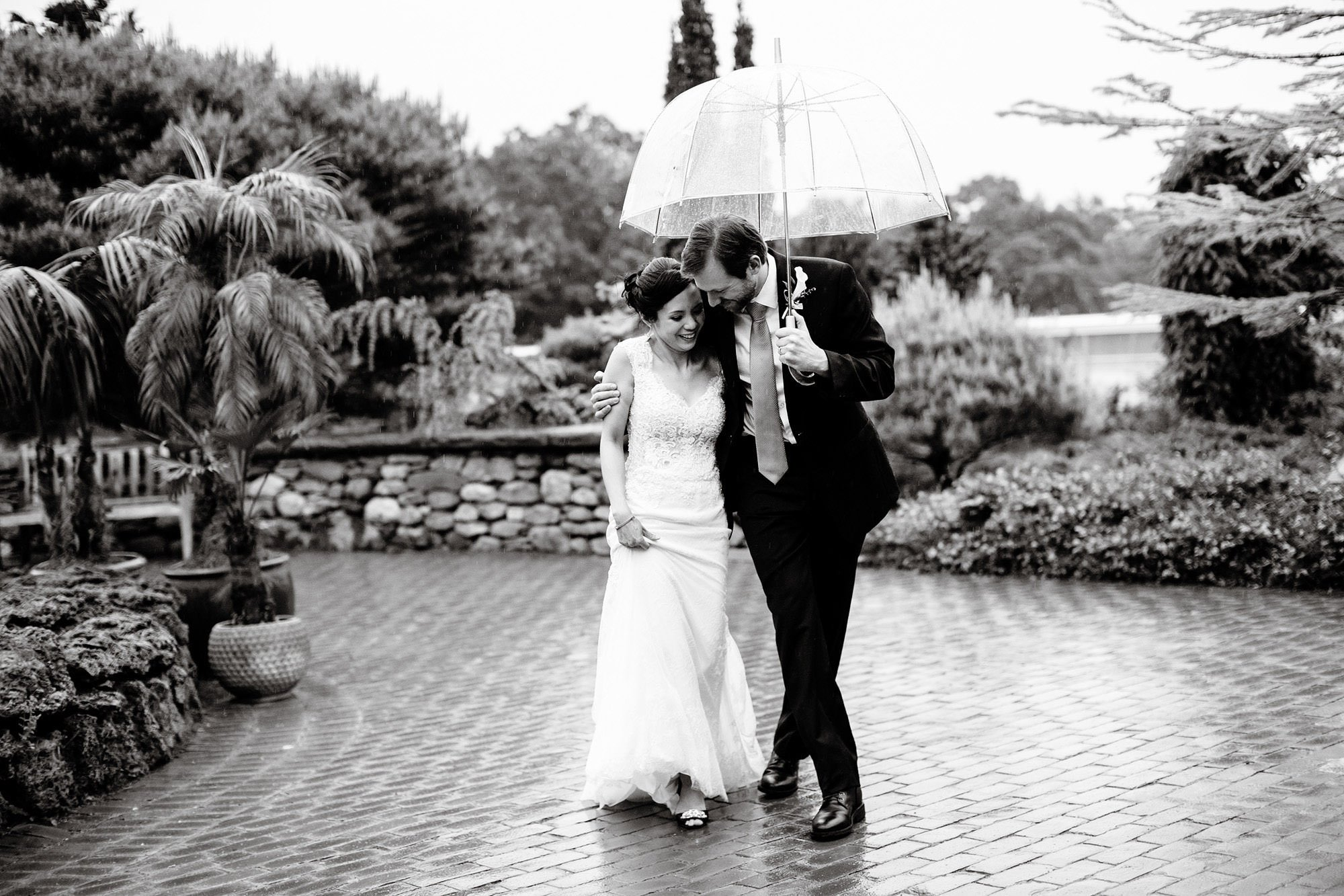The couple walk in the rain during their Tower Hill Botanic Garden Wedding.