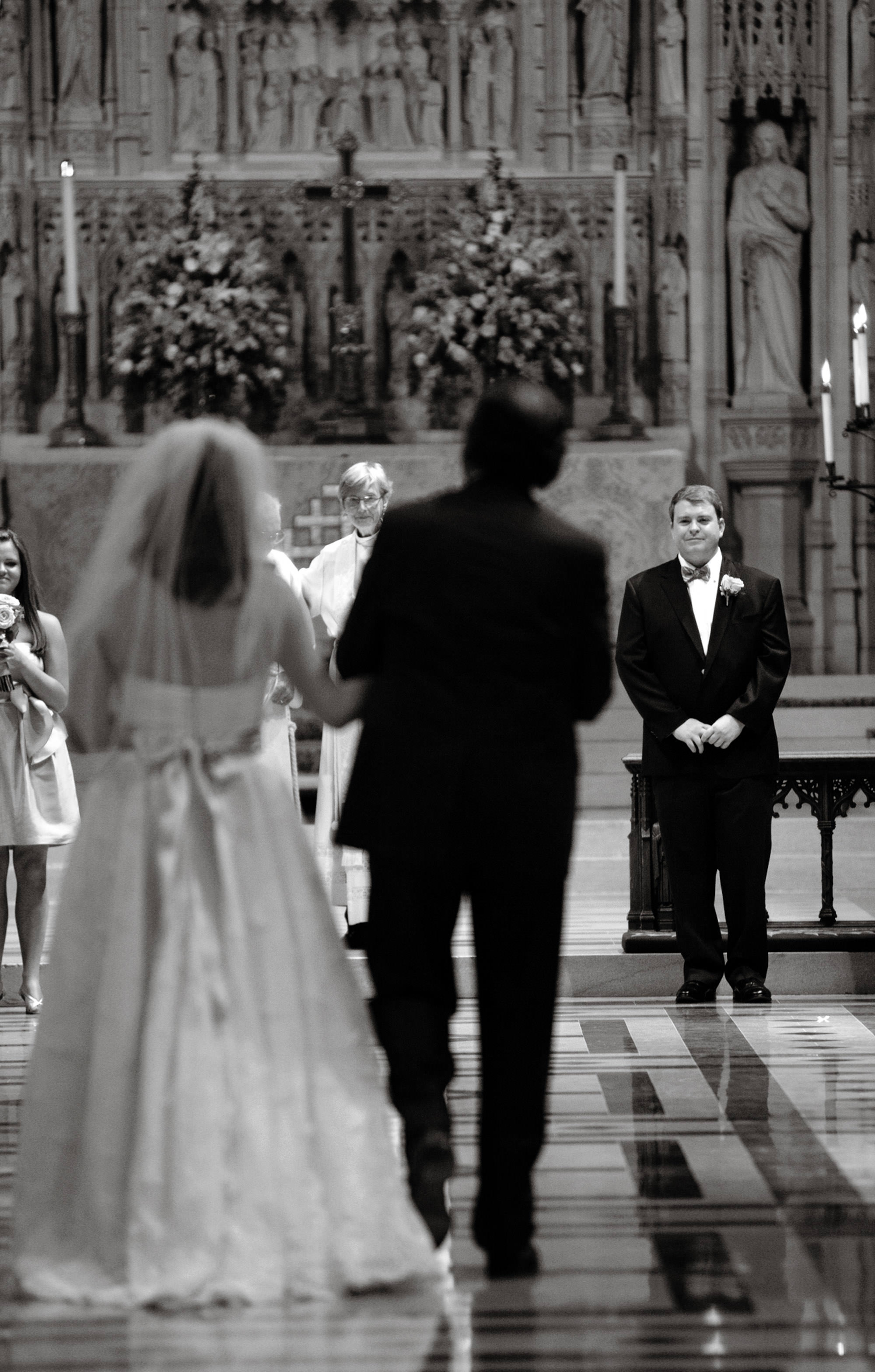 The groom sees his bride as she walks down the aisle during the Washington National Cathedral wedding.