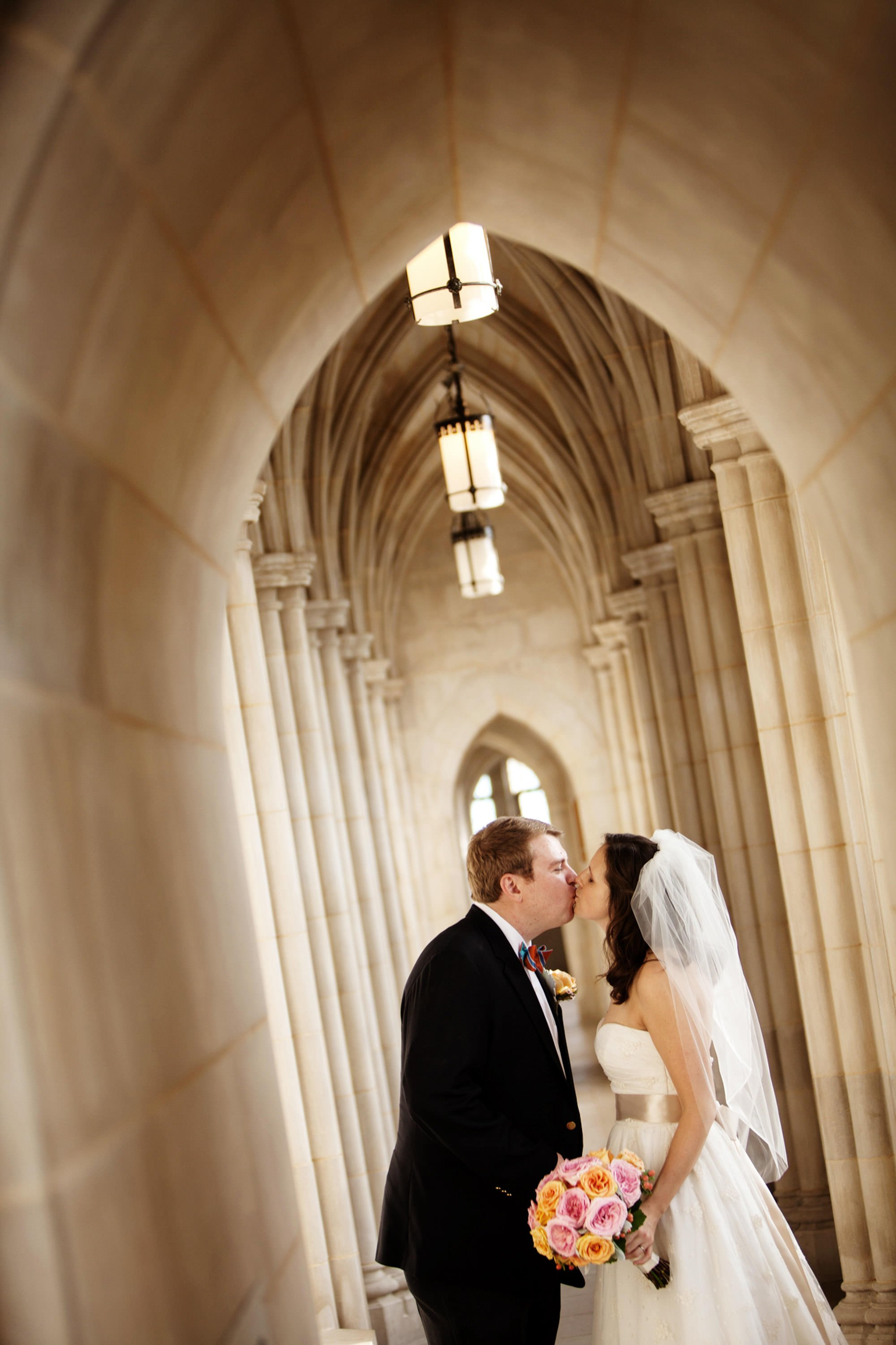 The bride and groom kiss on the Observation Deck on their Washington National Cathedral wedding day.