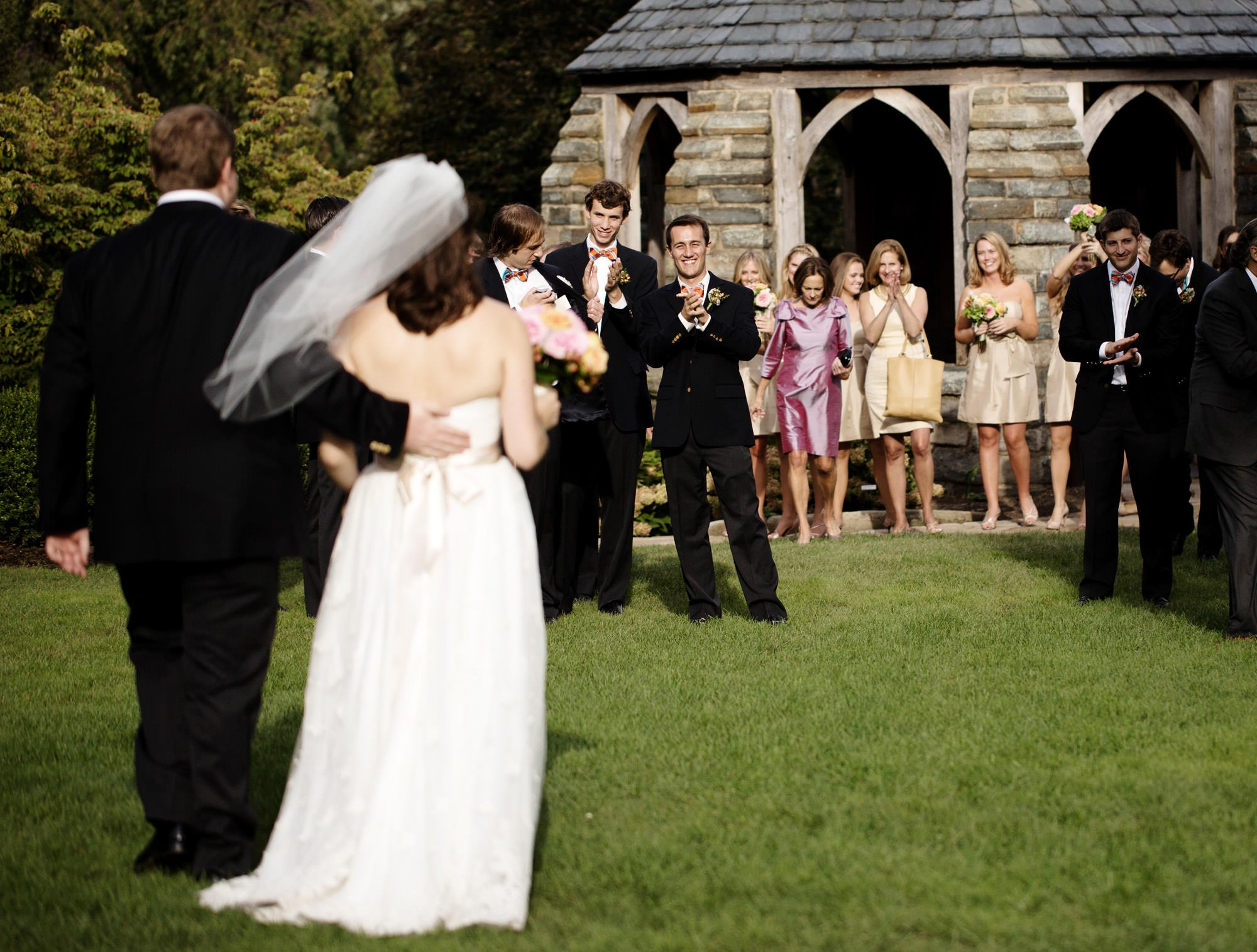 The bride and groom are greeted by the wedding party in the flower garden outside of the Washington National Cathedral.
