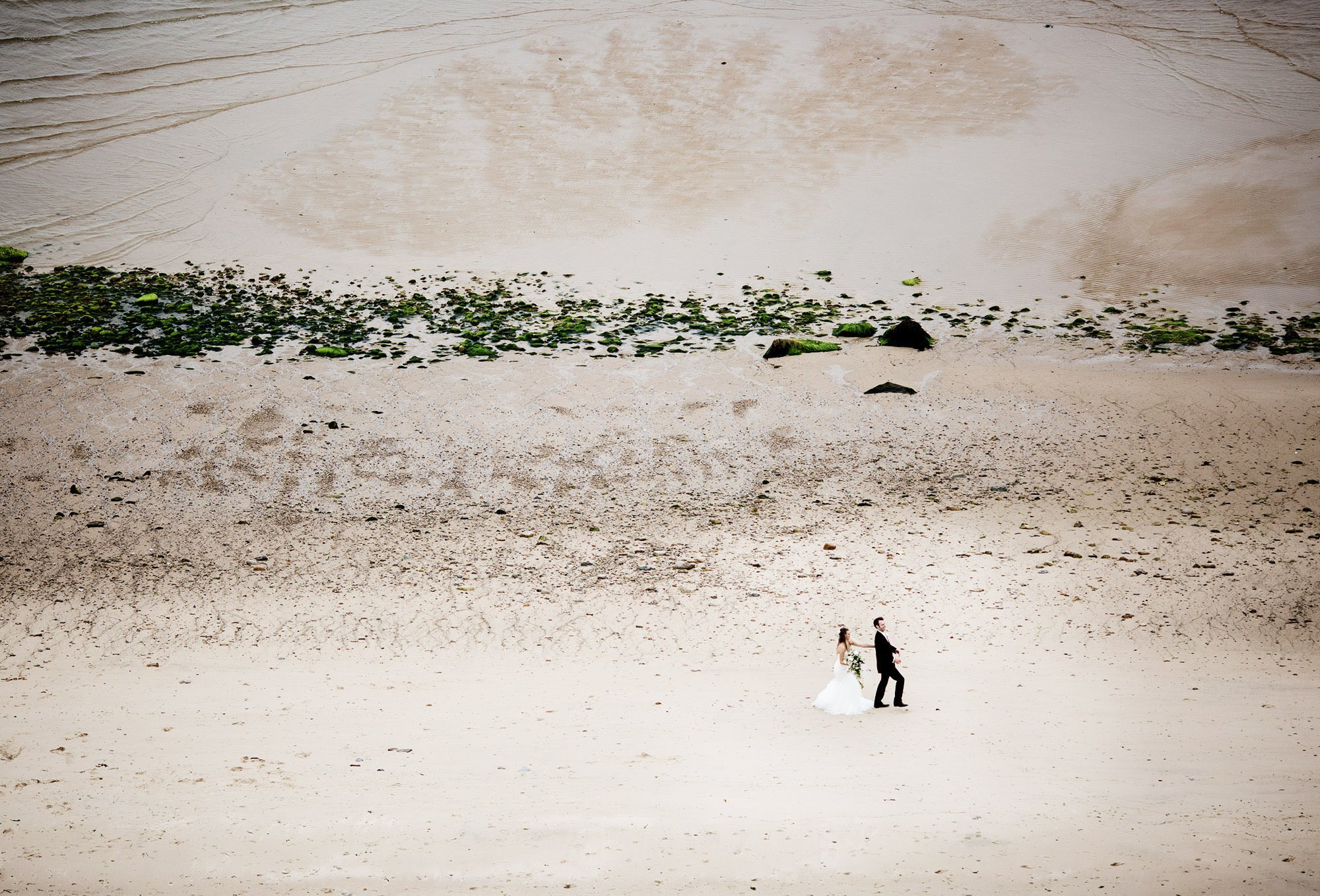 The bride and groom walk down the beach during the cocktail hour of their White Cliffs Country Club wedding.