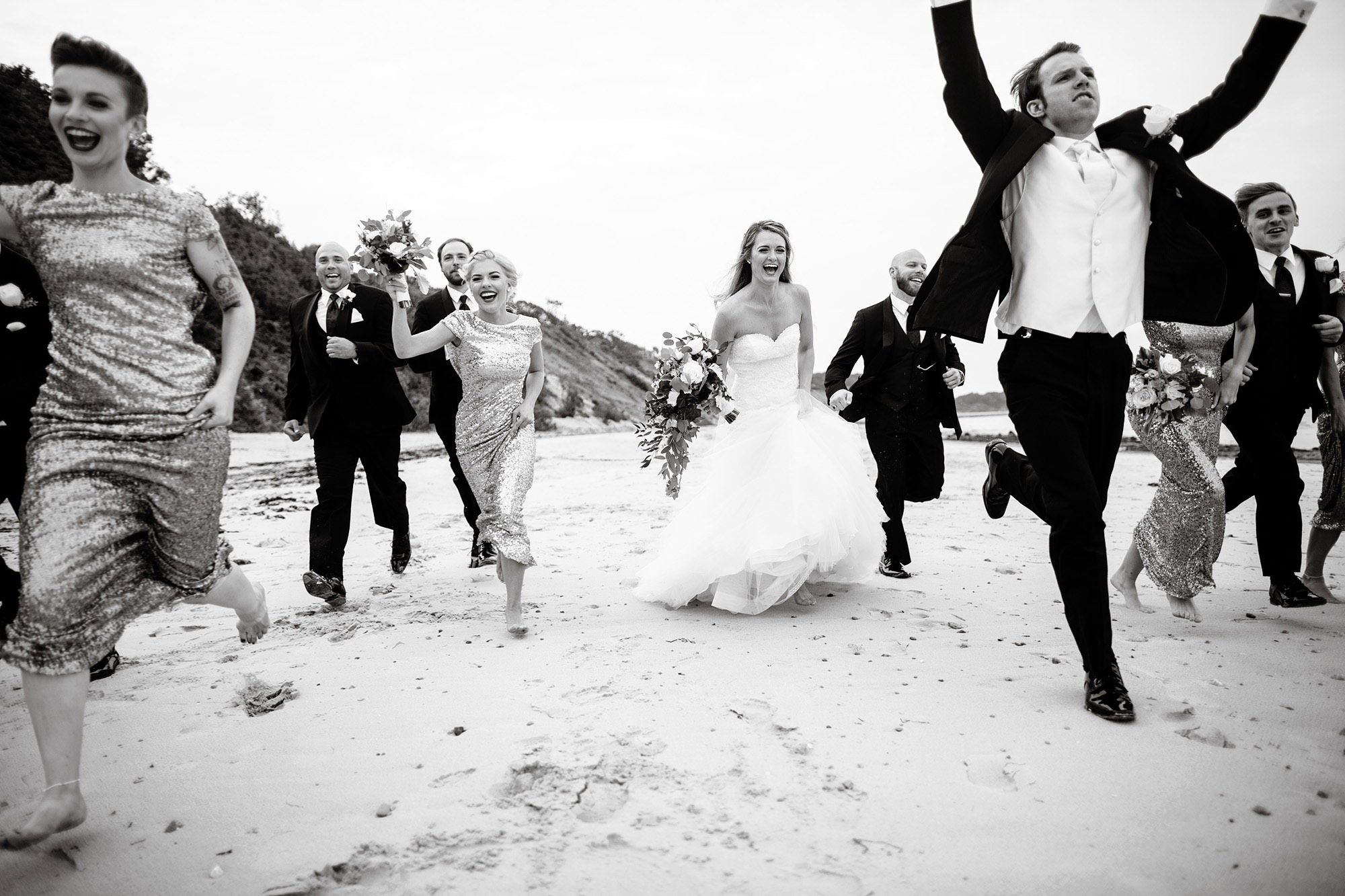 The wedding party runs down the beach during the cocktail hour at White Cliffs Country Club.