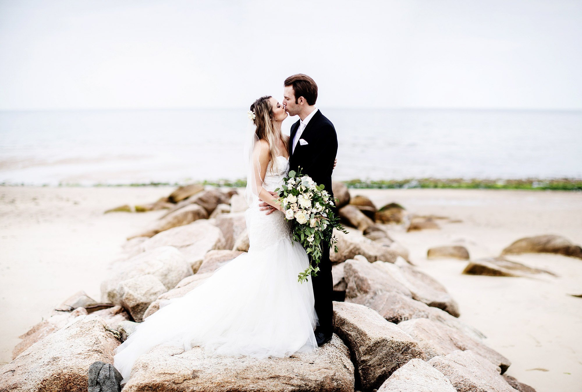 The couple kiss on the rocks during their White Cliffs Country Club wedding.