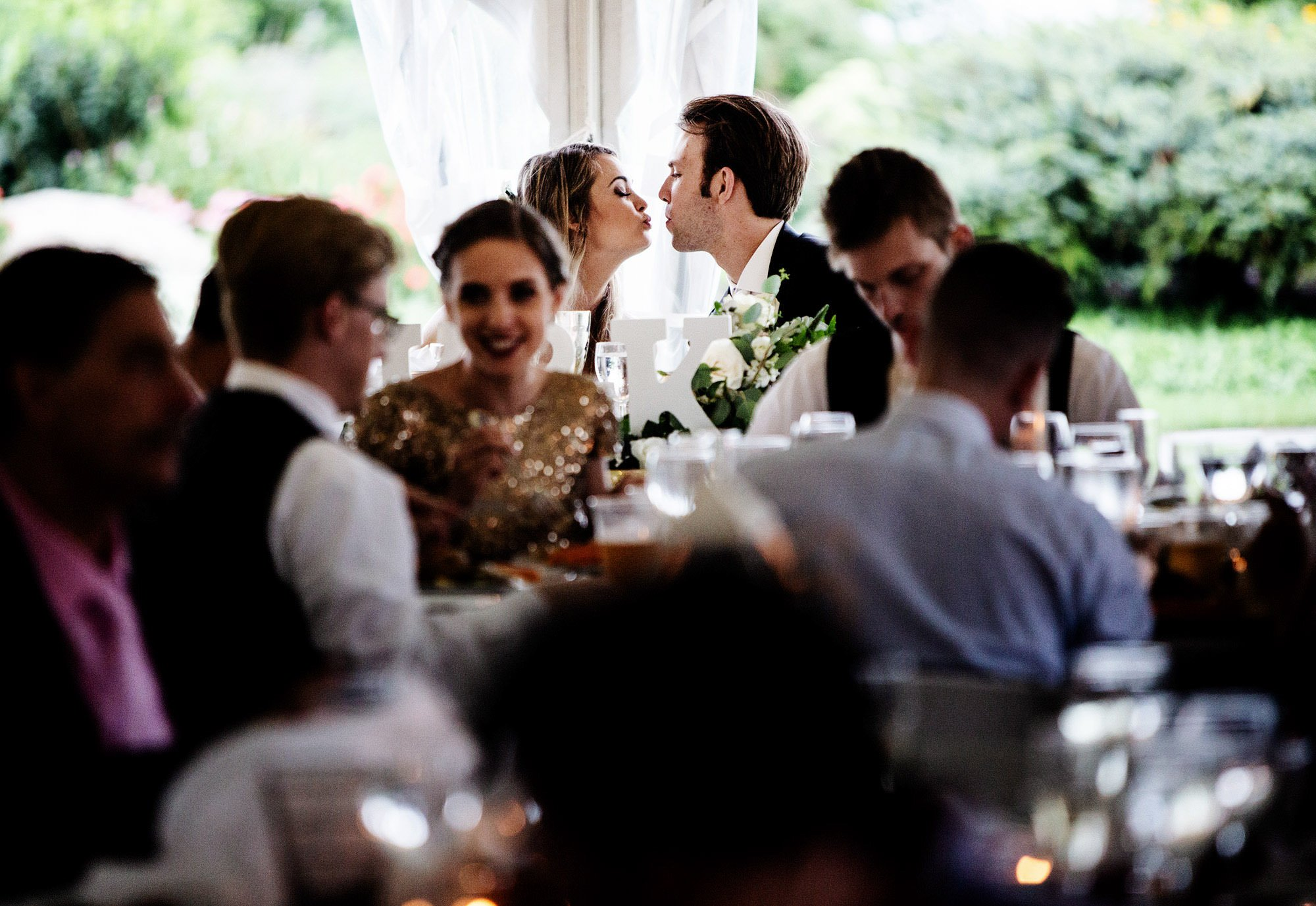 The bride and groom kiss during dinner on their White Cliffs Country Club wedding day.