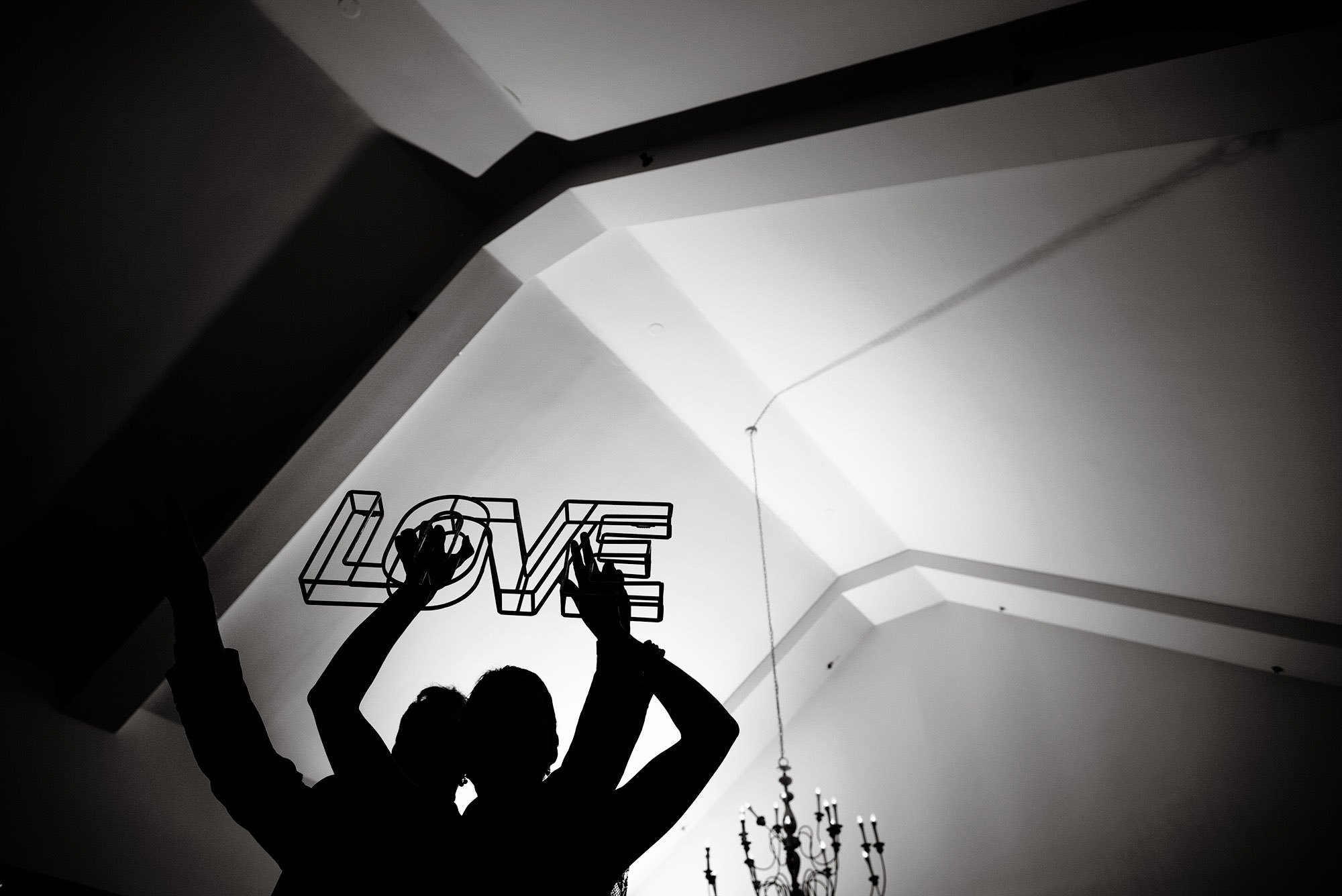 A LOVE sign is held high during the White Cliffs Country Club wedding reception.