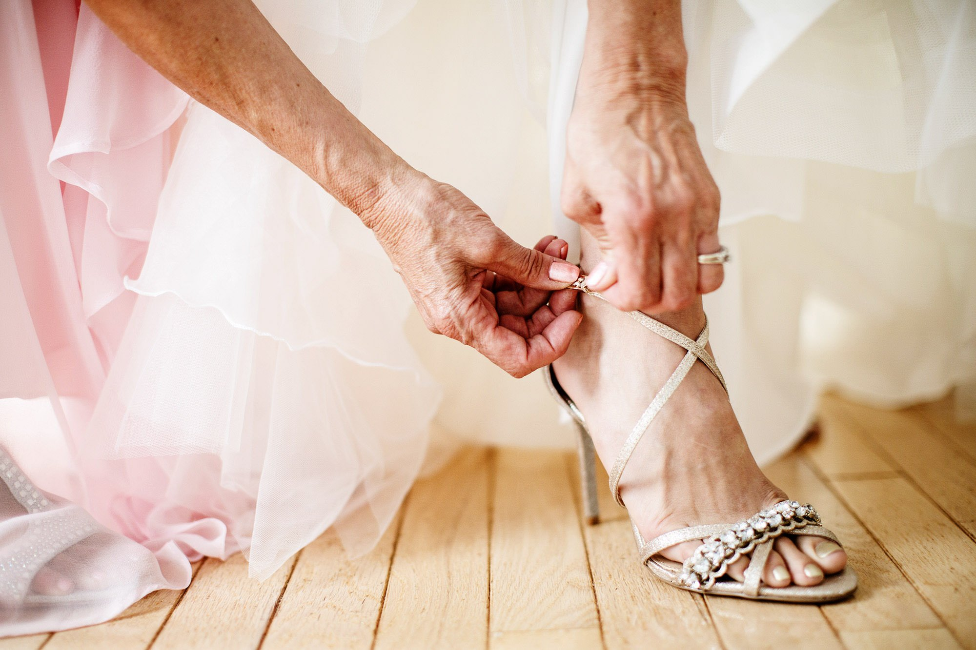 The bride puts on her shoes before her White Cliffs Country Club Wedding ceremony.