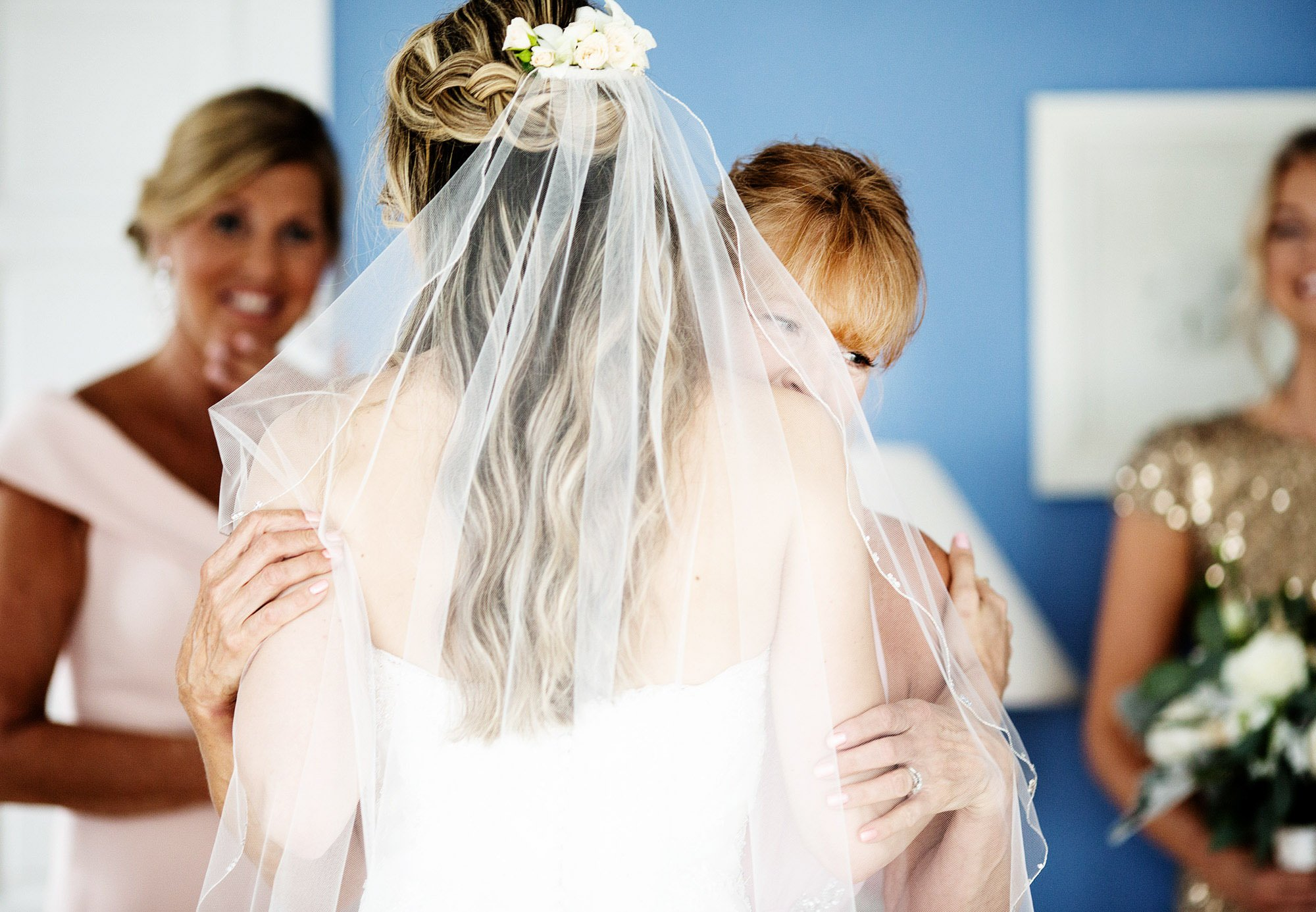 The bride is hugged by her mother on her White Cliffs Country Club Wedding day.