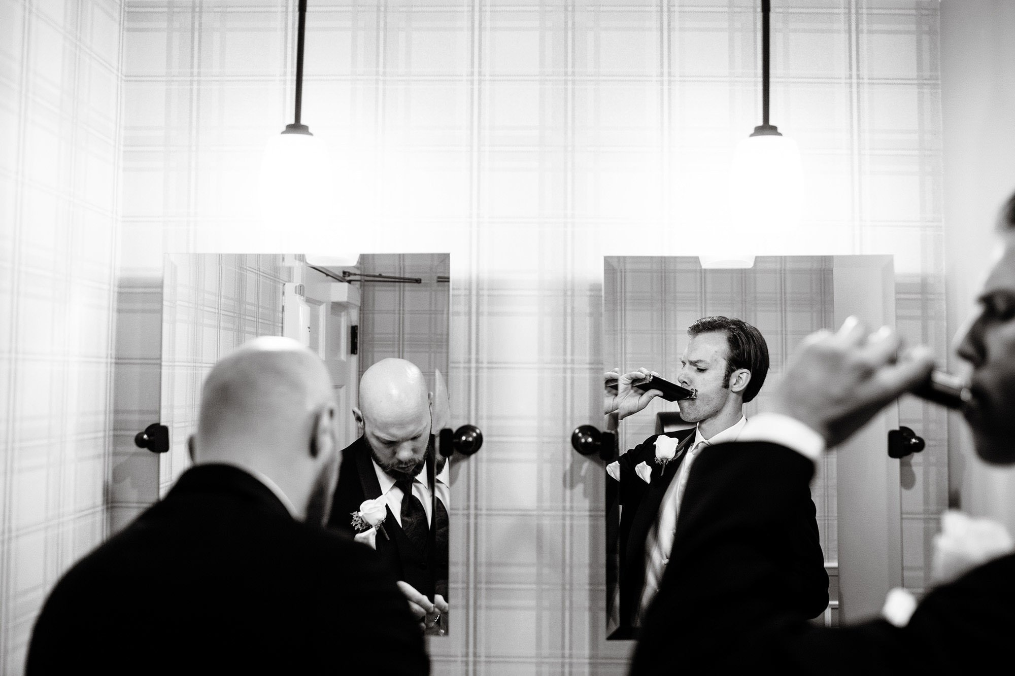 The groom gets ready with his groomsmen in a bathroom before his White Cliffs Country Club Wedding ceremony.