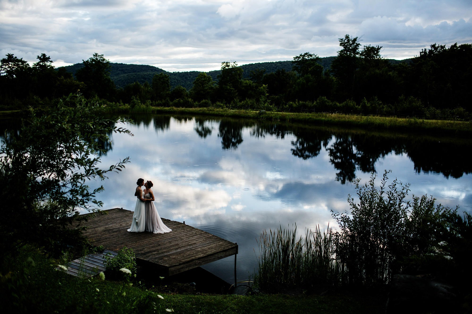 Vermont Wedding Photographers I Two brides kiss on the dock of The Ponds at Bolton Valley.