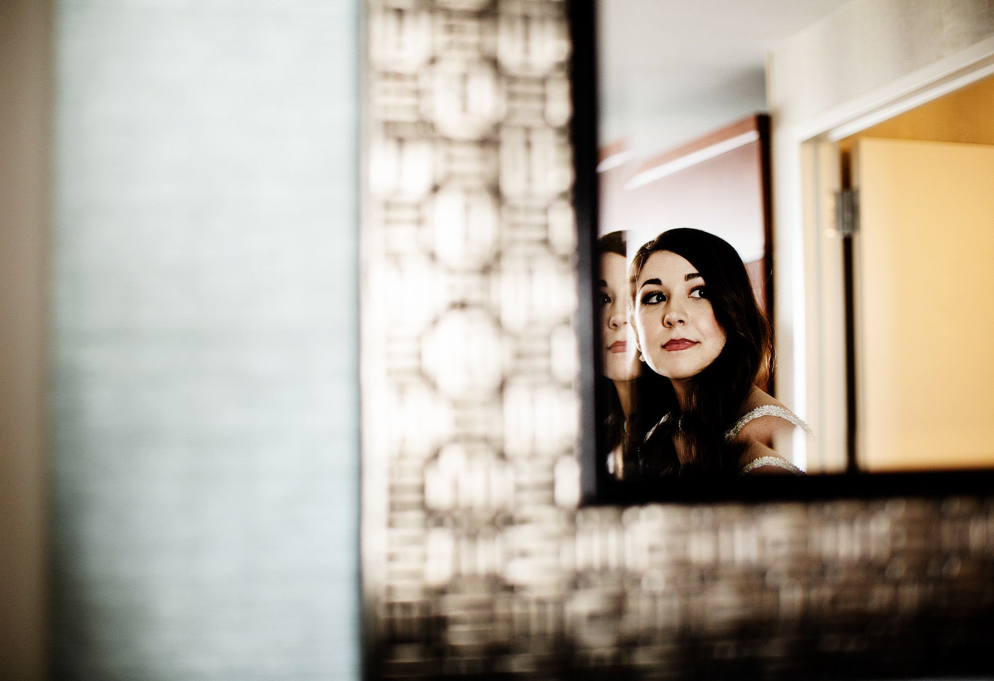 The bride looks at herself in the mirror before her American Institute of Architects Wedding ceremony.