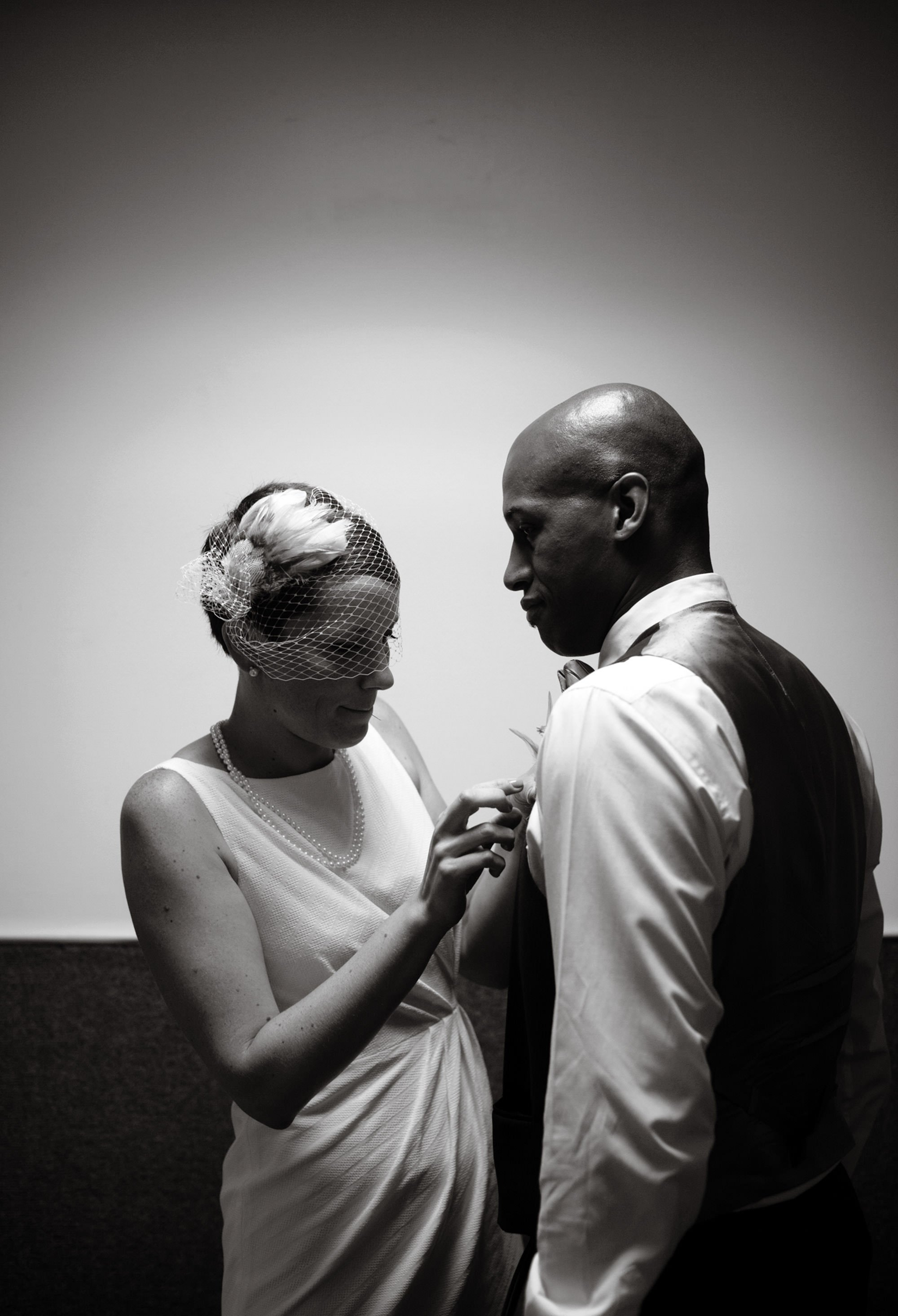 The bride puts on her groom's boutonniere before the DC Courthouse wedding ceremony.