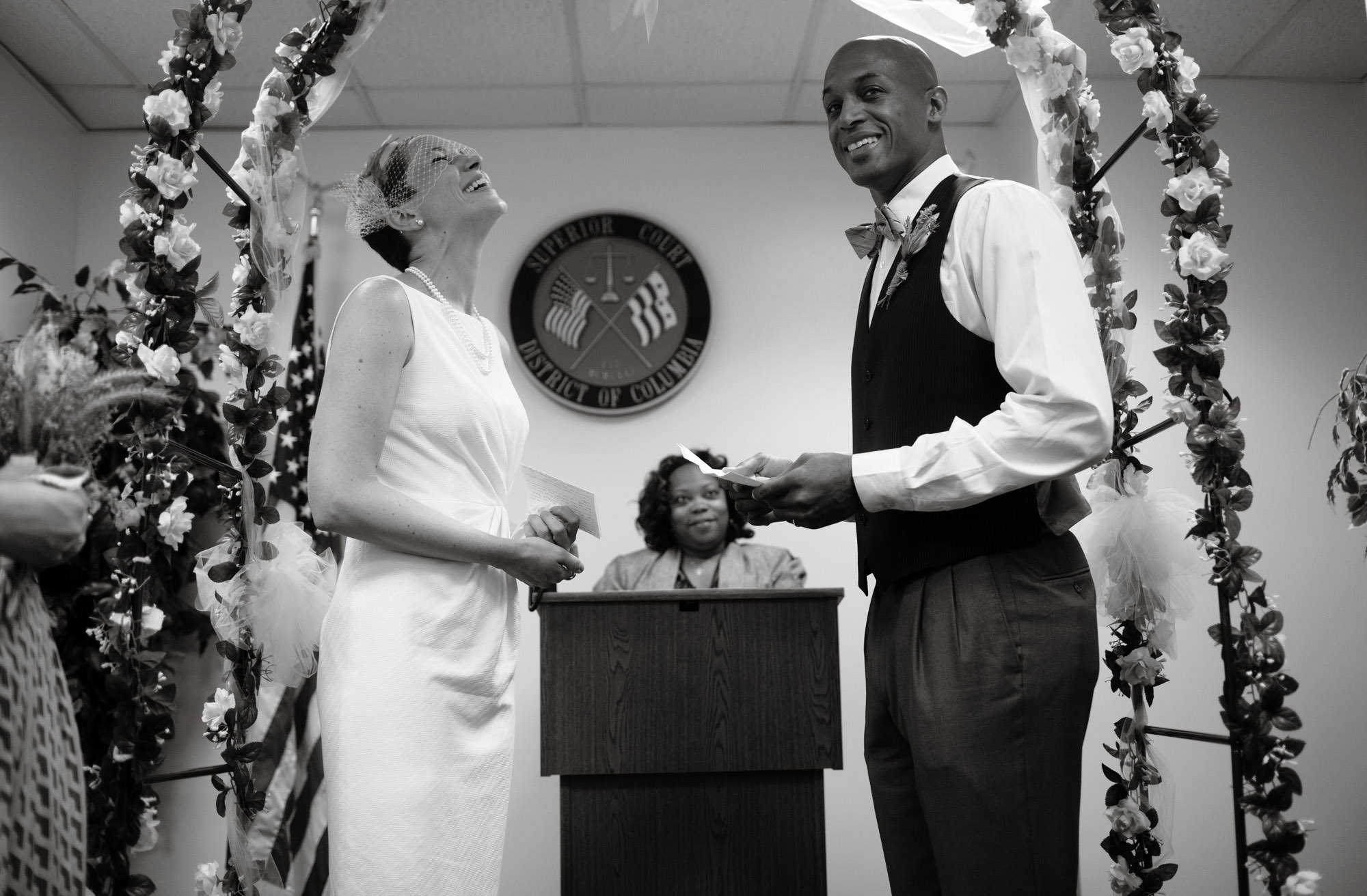 The bride and groom smile while giving vows during the DC Courthouse wedding ceremony.