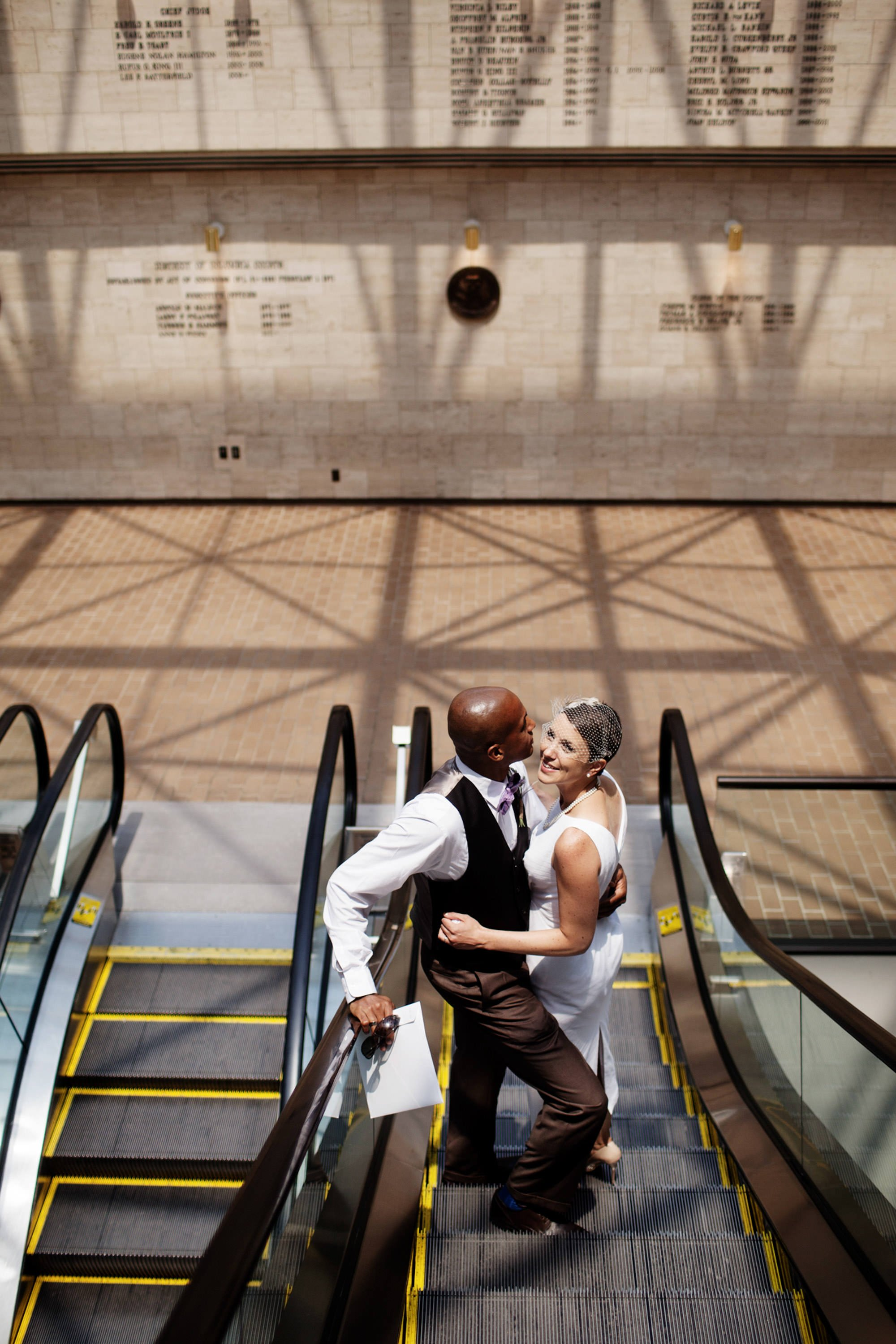 The bride and groom ride down the escalator following their DC Courthouse wedding ceremony.