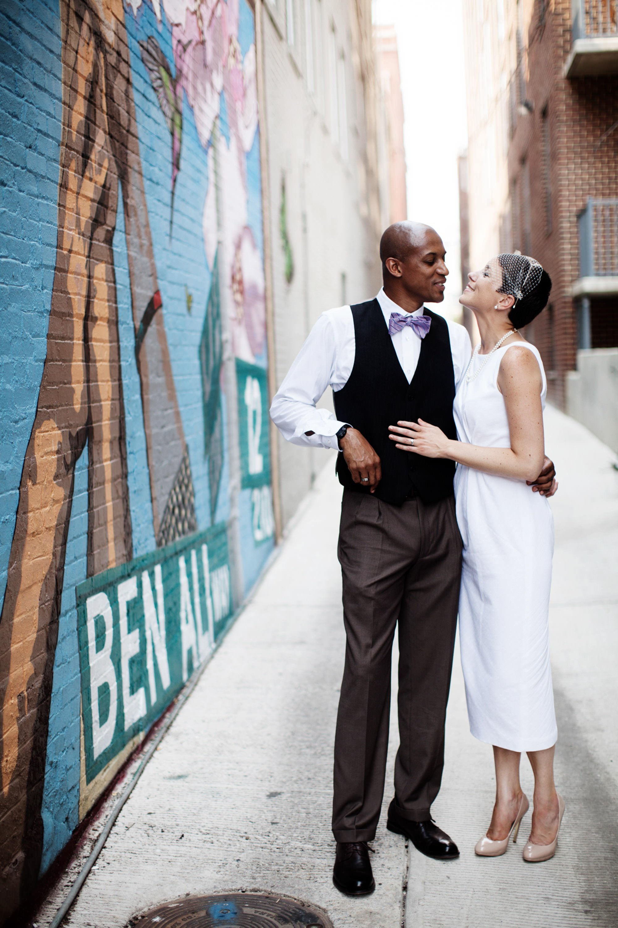 Ben's Chili Bowl wedding  I  The bride and groom pose by a mural in an alley just outside the iconic restaurant in Washington, DC.