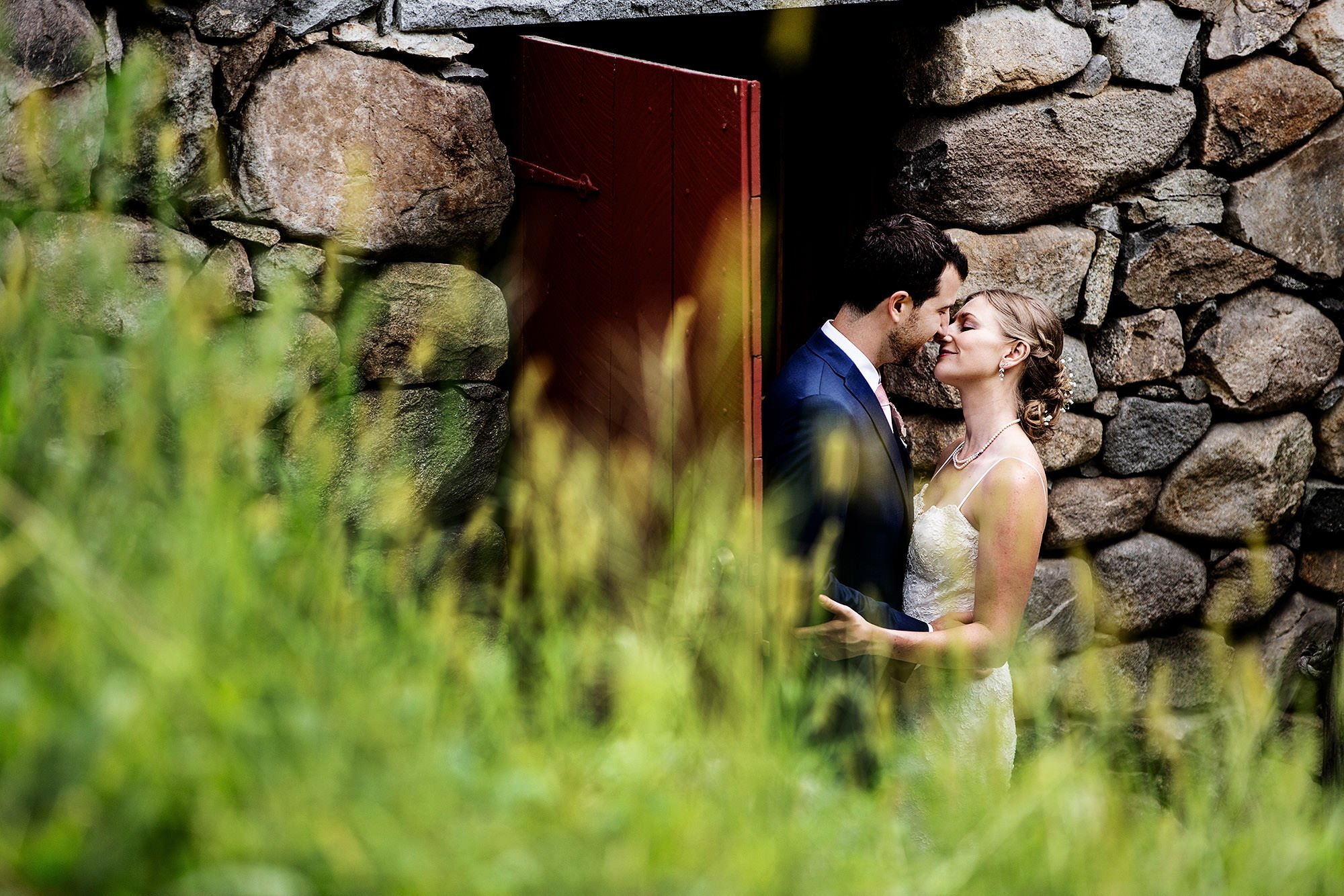 Wayside Inn Wedding  I  The couple kiss at the Grist Mill in Sudbury, MA.