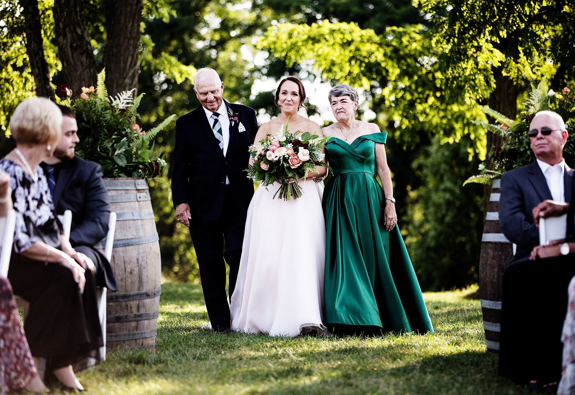 Red Maple Vineyard Wedding  I  The bride is escorted down the aisle by her parents.