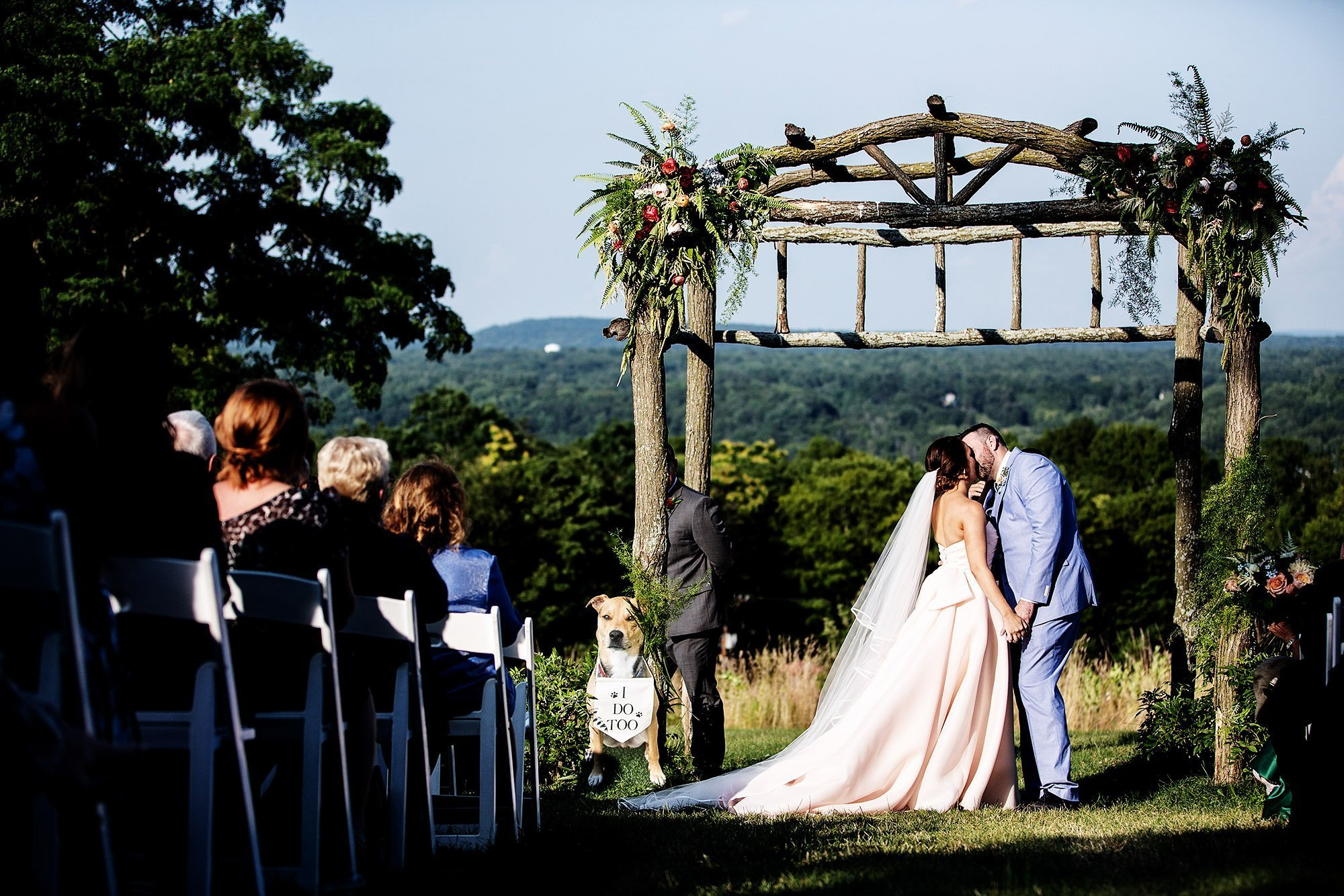 Red Maple Vineyard Wedding  I  The bride and groom share their first kiss during their outdoor wedding ceremony in Upstate New York.