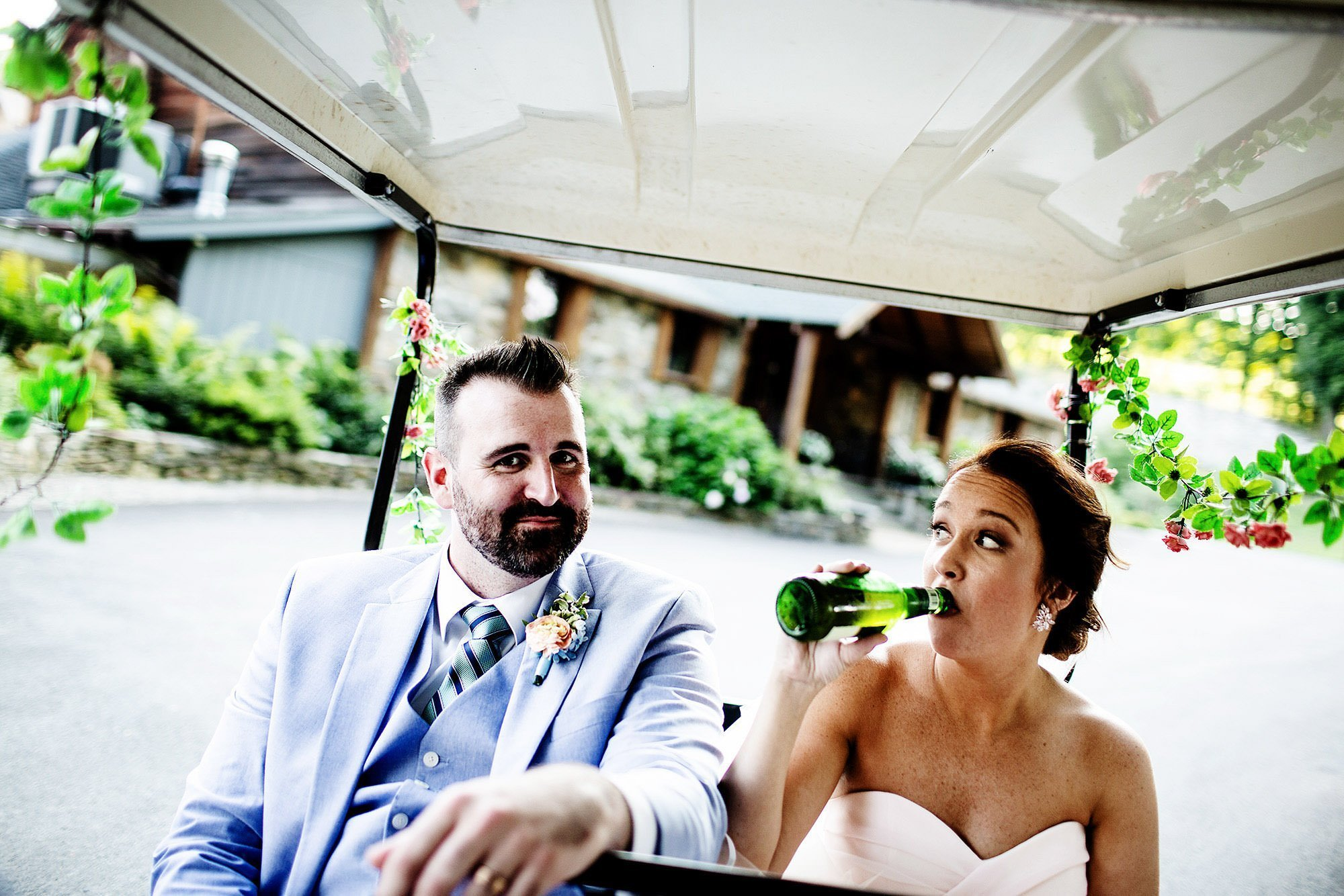 Red Maple Vineyard Wedding  I  The bride and groom ride a golf cart while drinking beer following their wedding ceremony.