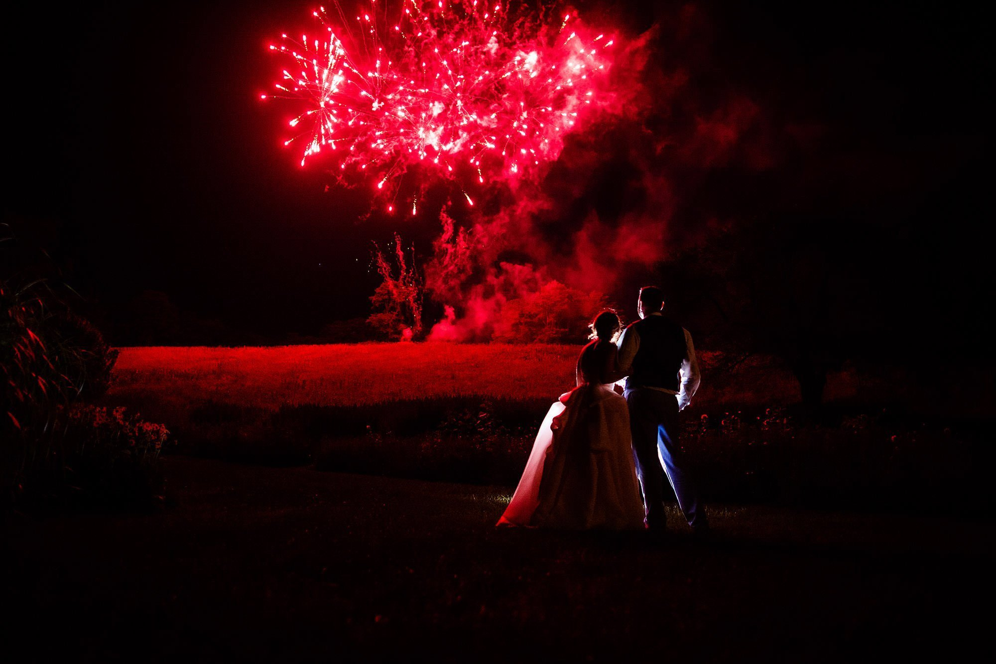 Red Maple Vineyard Wedding  I  The bride and groom watch fireworks during their reception on their wedding day in Upstate New York.