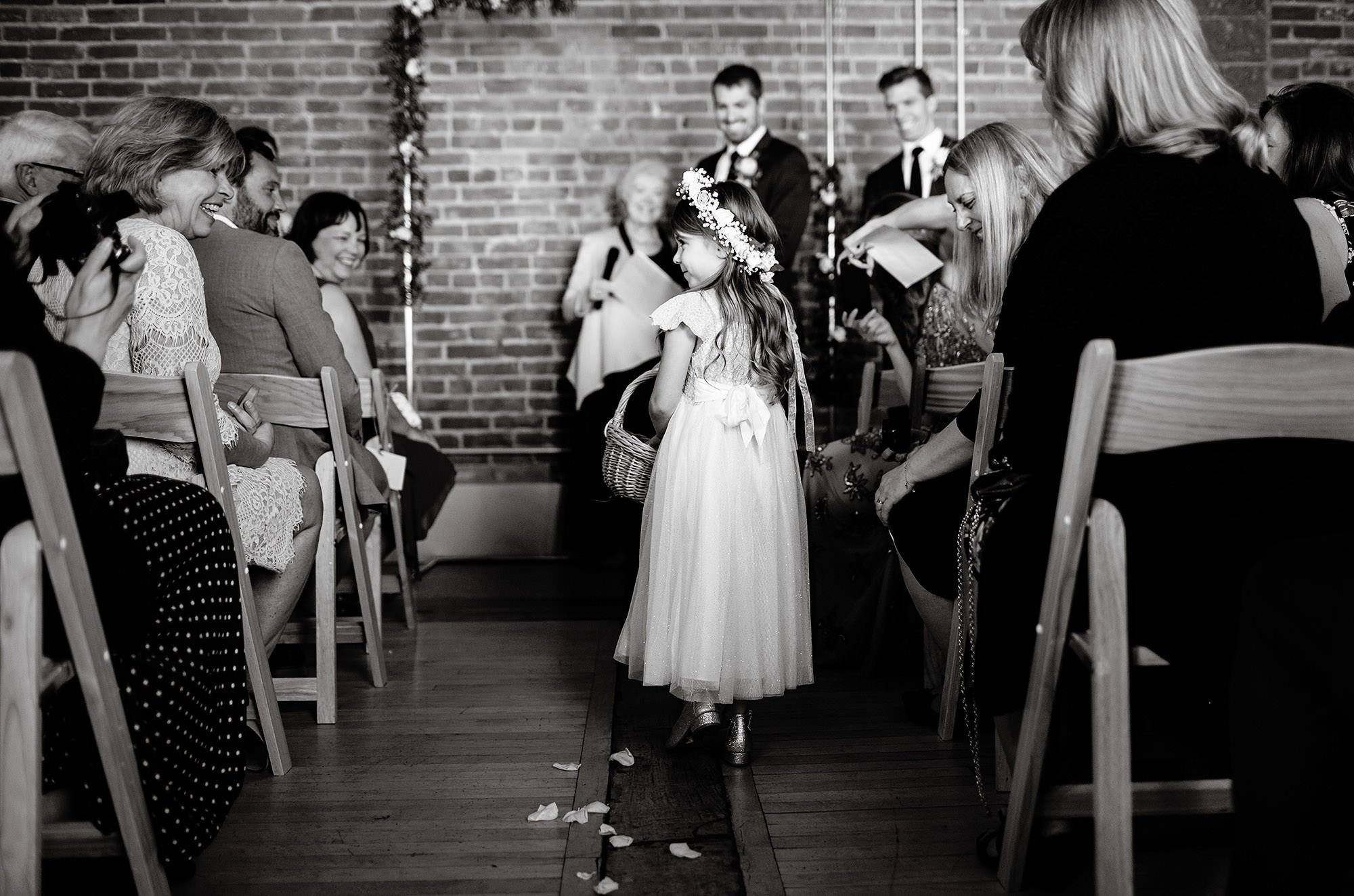 Loft at 600 F Wedding  I  A flower girl walks down the aisle during the wedding ceremony.