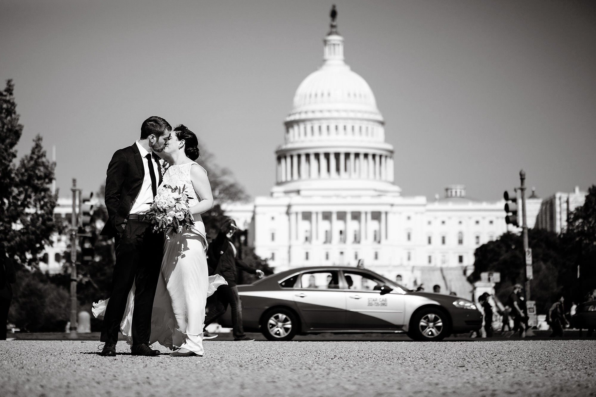 Loft at 600 F Wedding  I  The bride and groom kiss in front of the Capitol Building in Washington, DC.