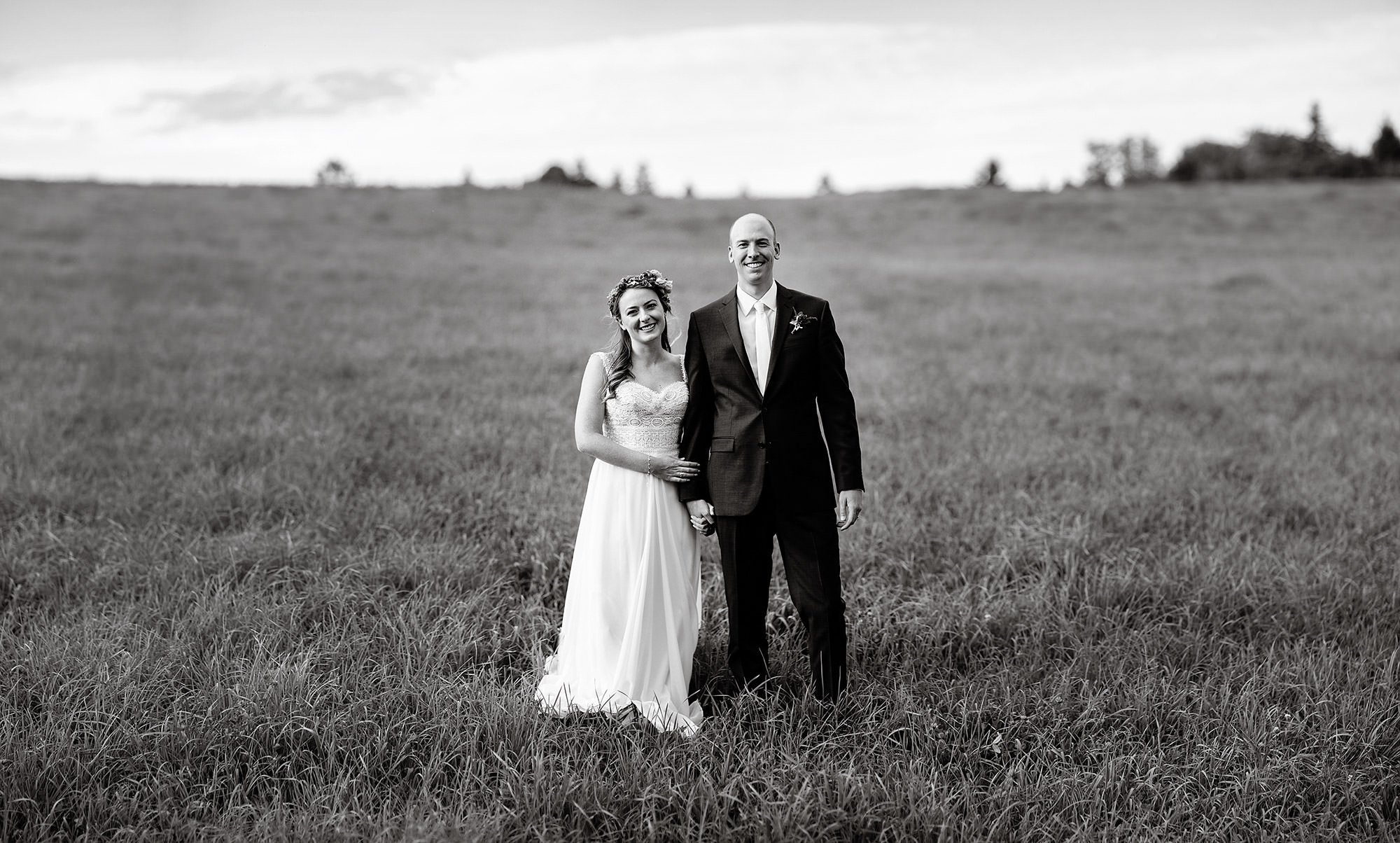 Vermont Family Farm Wedding  I  The bride and groom pose in a field on their wedding day.