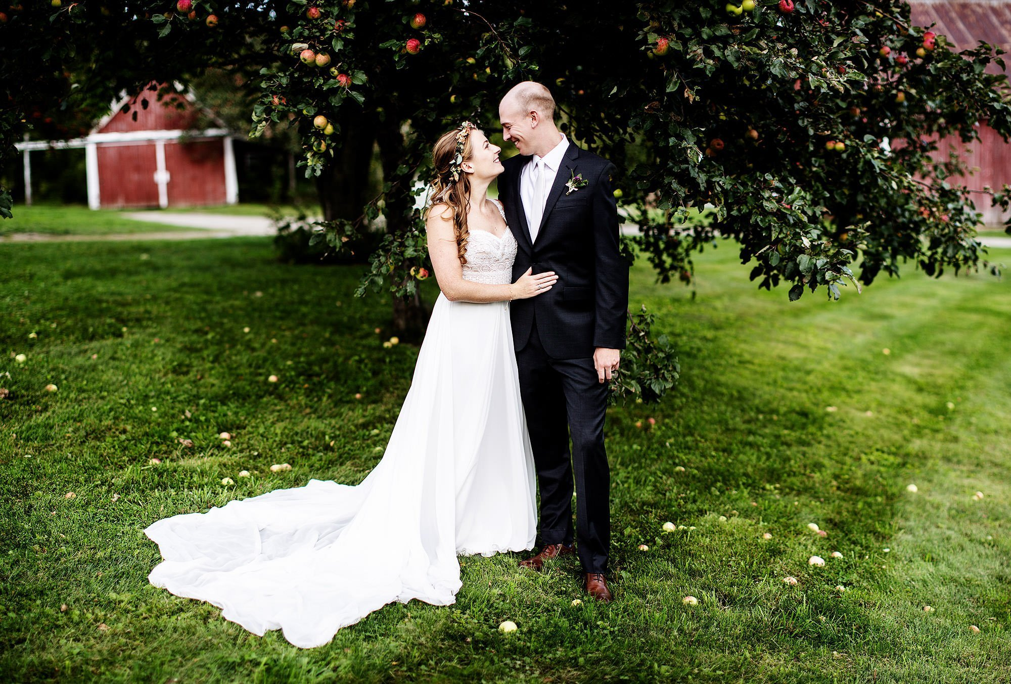 Vermont Family Farm Wedding  I  The bride and groom pose in front of an apple tree.