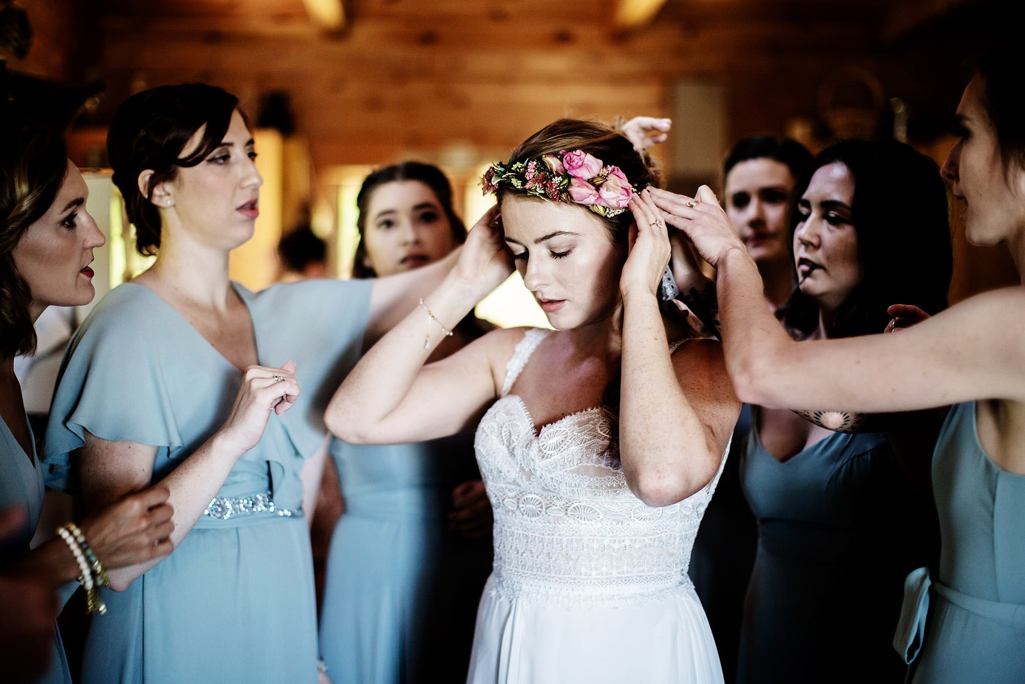 Vermont Family Farm Wedding  I  The bride is helped by her bridesmaids to put flowers in her hair.