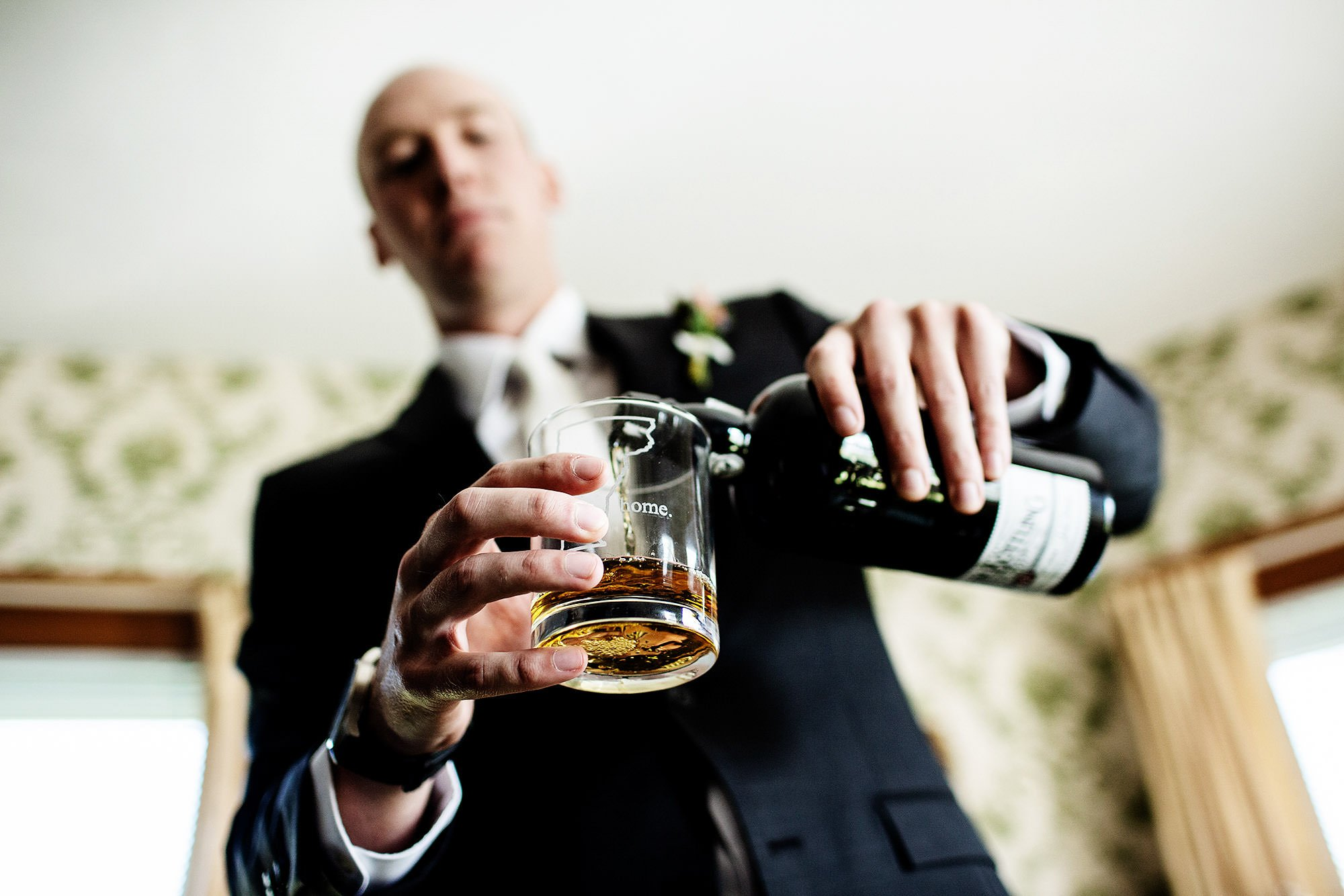 Vermont Family Farm Wedding  I  The groom pours shots for his groomsmen.