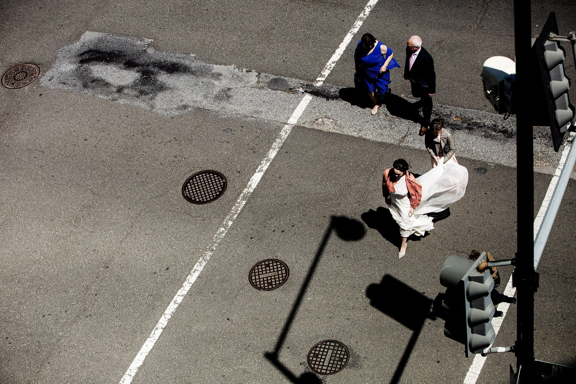 Loft at 600 F Wedding  I  The bride walks through a crosswalk with her family in Washington, DC.