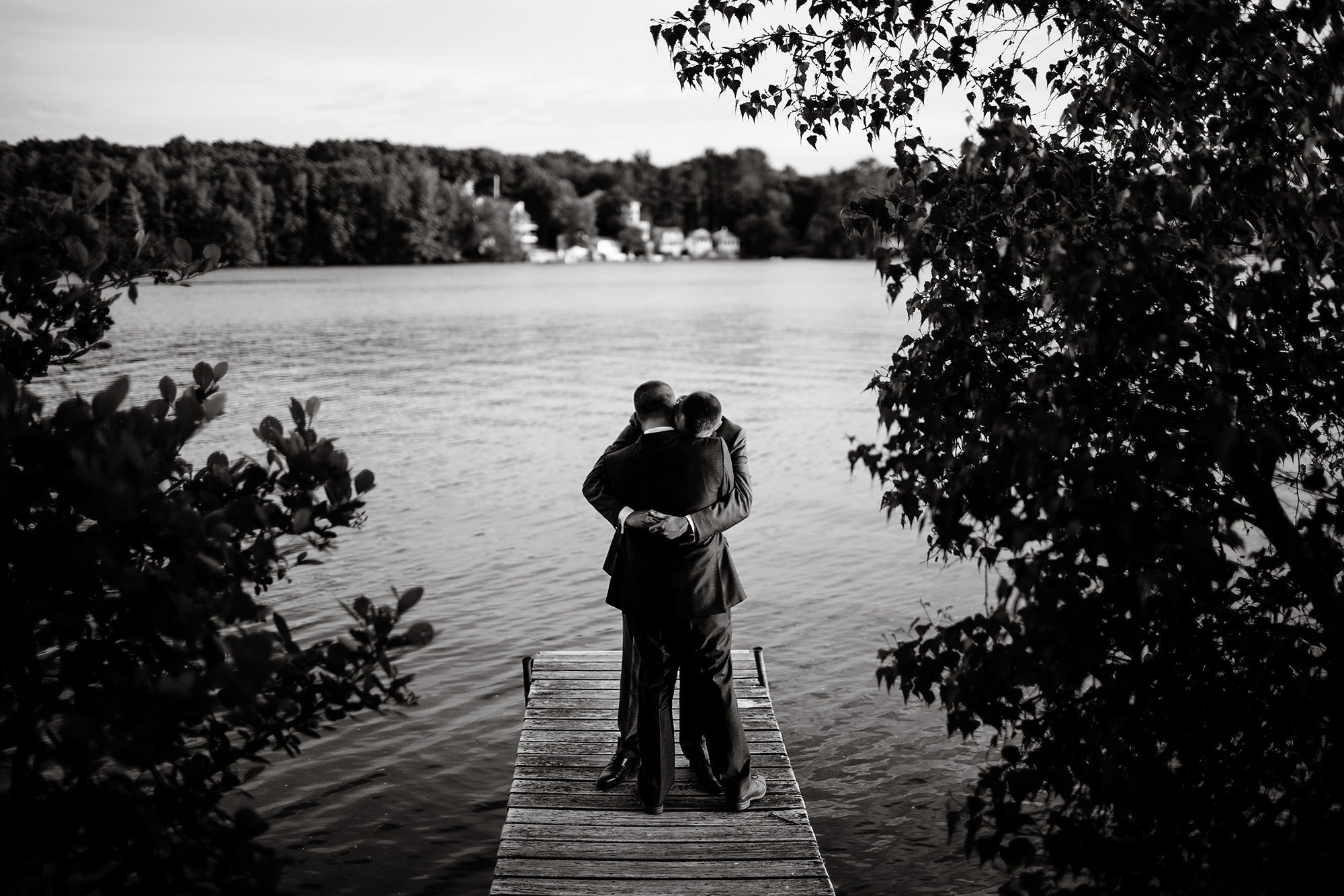 Lake Pearl Wrentham Wedding  I  The grooms hug on the dock of Lake Pearl at sunset after the wedding ceremony.