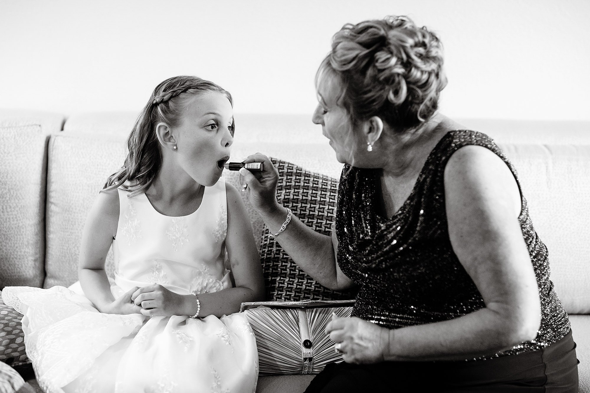 Lake Pearl Wrentham Wedding  I  A flower girl puts on lipstick before the ceremony.