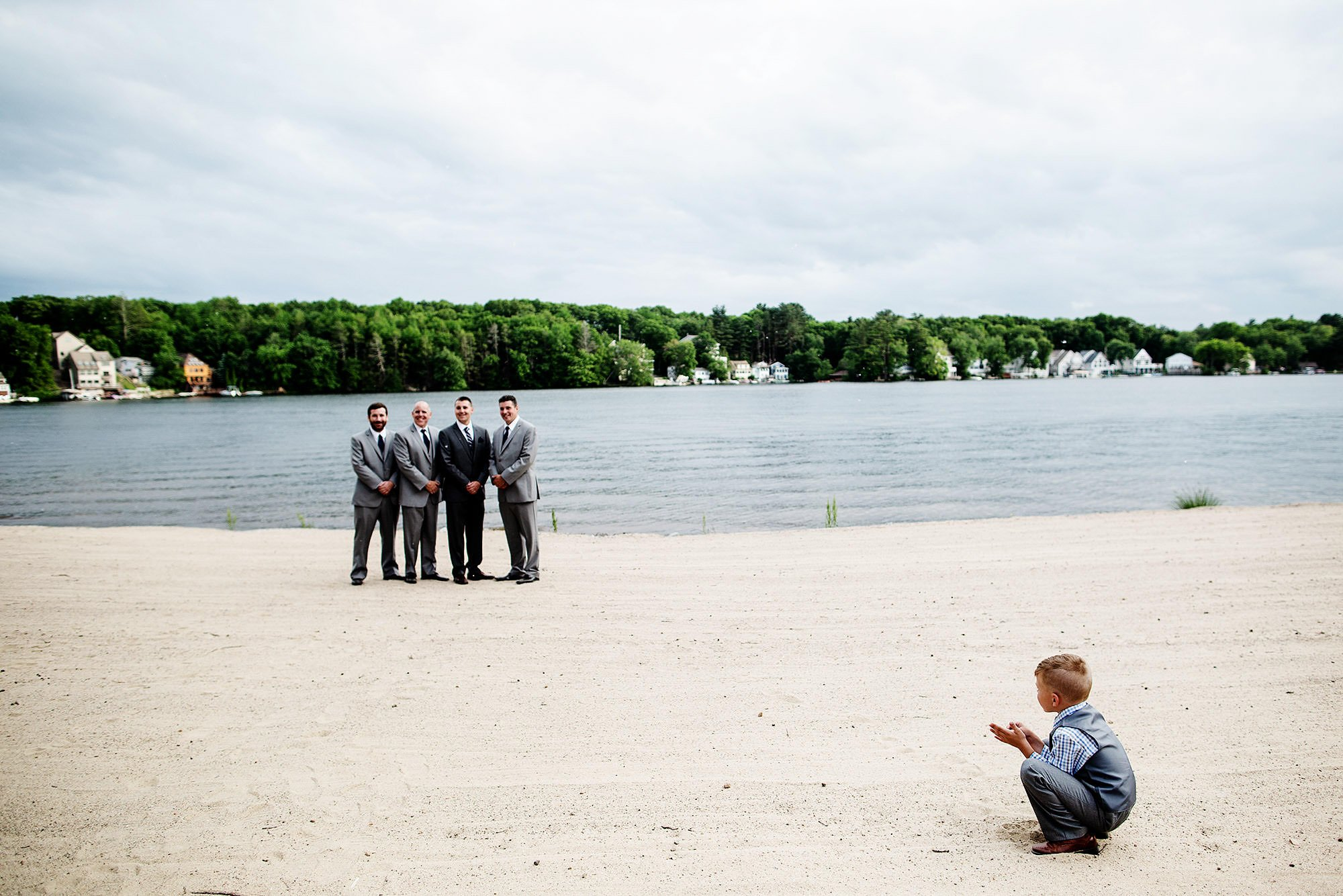 Lake Pearl Wrentham Wedding  I  A ring bearer watches as portraits are taken of the groomsmen.