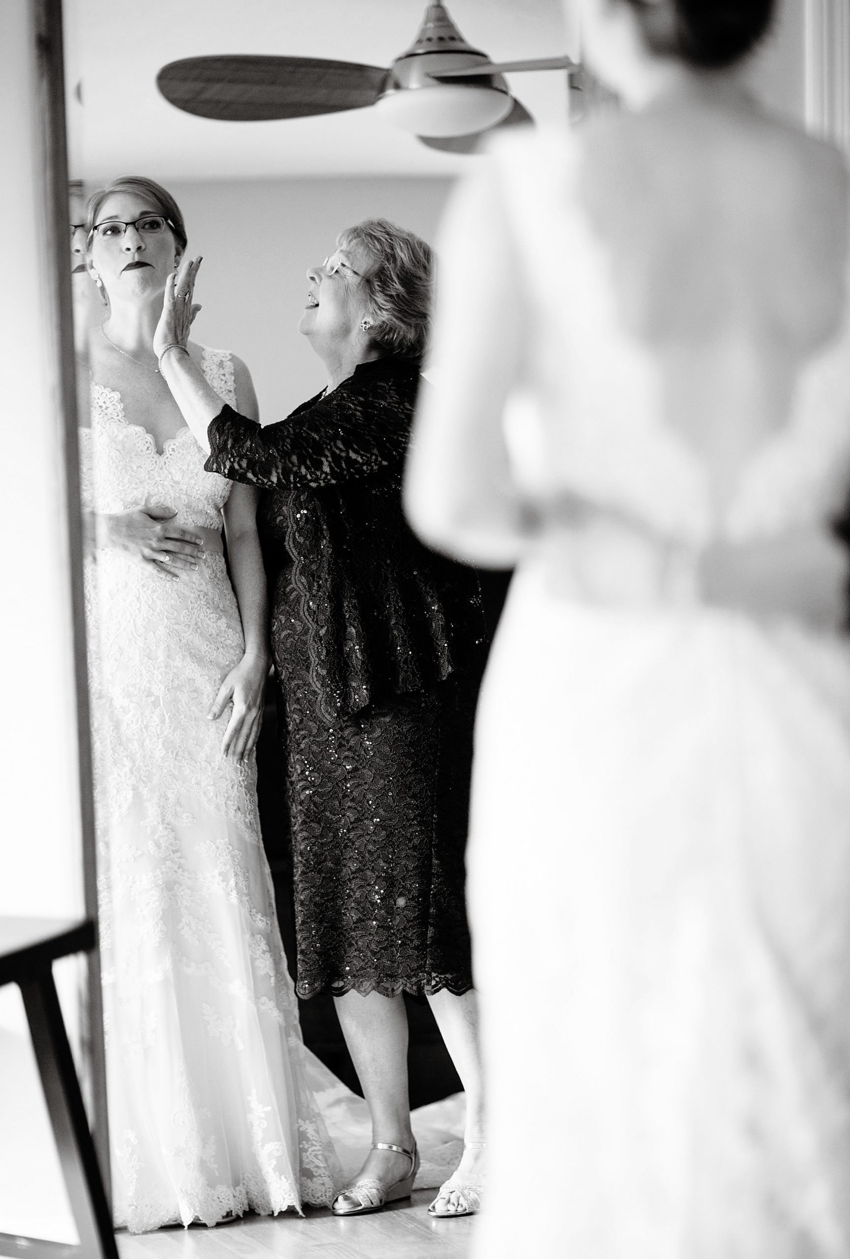 Massachusetts Backyard Wedding  I  The bride looks in the mirror with her mother before the wedding ceremony.