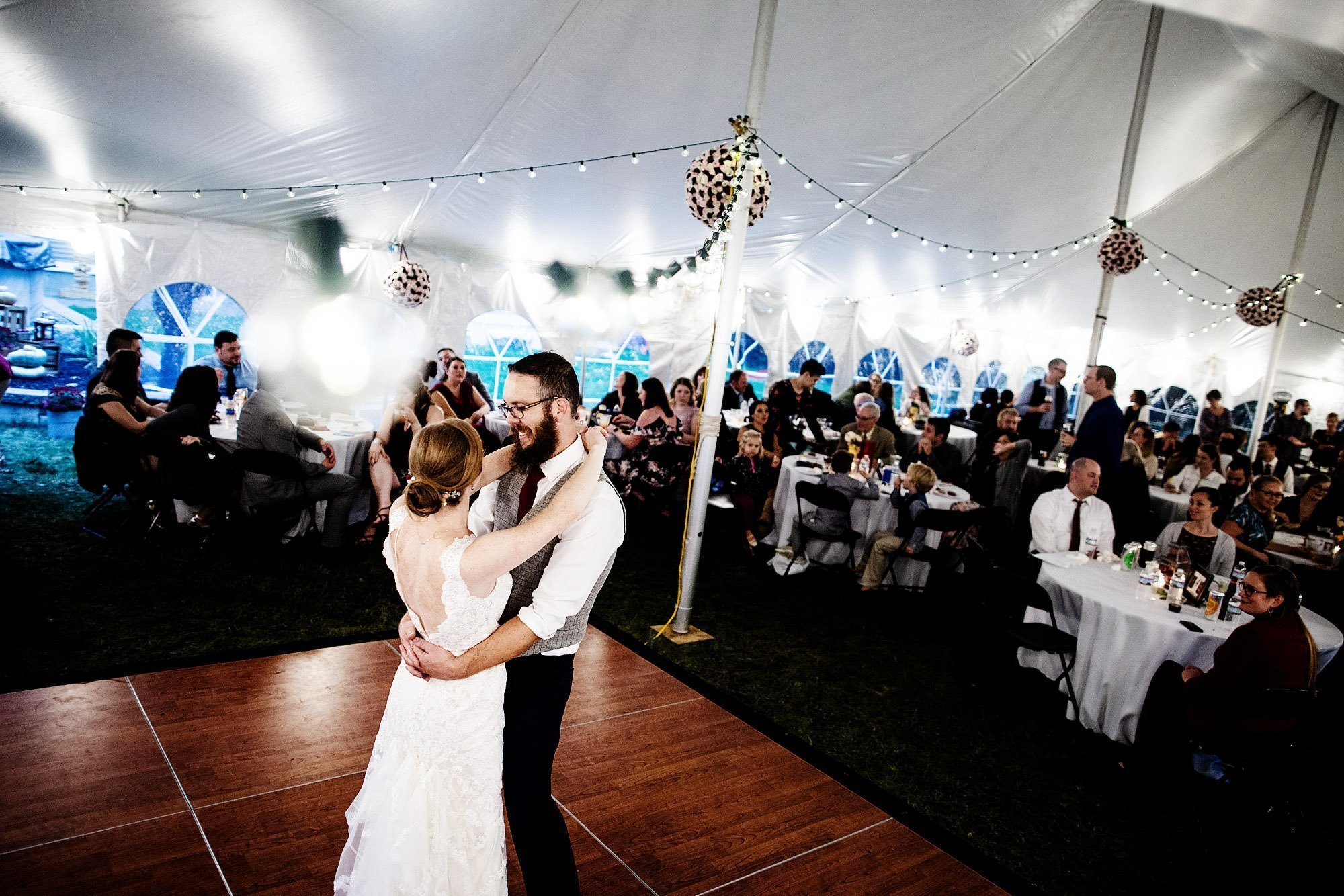 Massachusetts Backyard Wedding  I  The bride and groom share their first dance during the tented wedding reception.