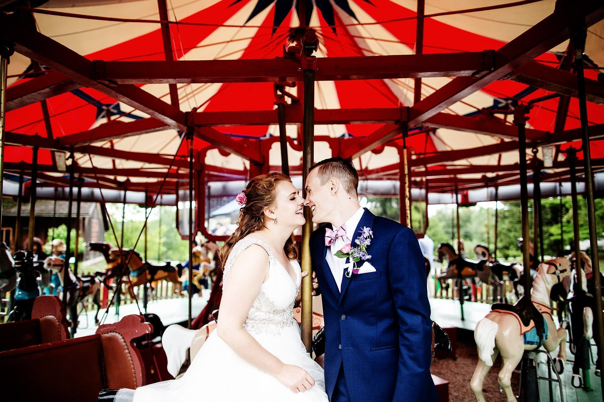 Shelburne Museum Wedding  I  The bride and groom kiss on the merry go round in Shelburne, VT.
